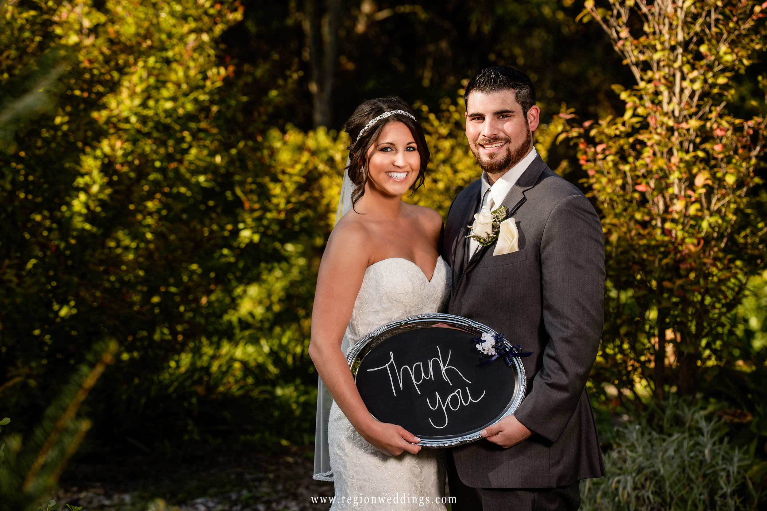 Bride and groom display their Thank You sign on wedding day.