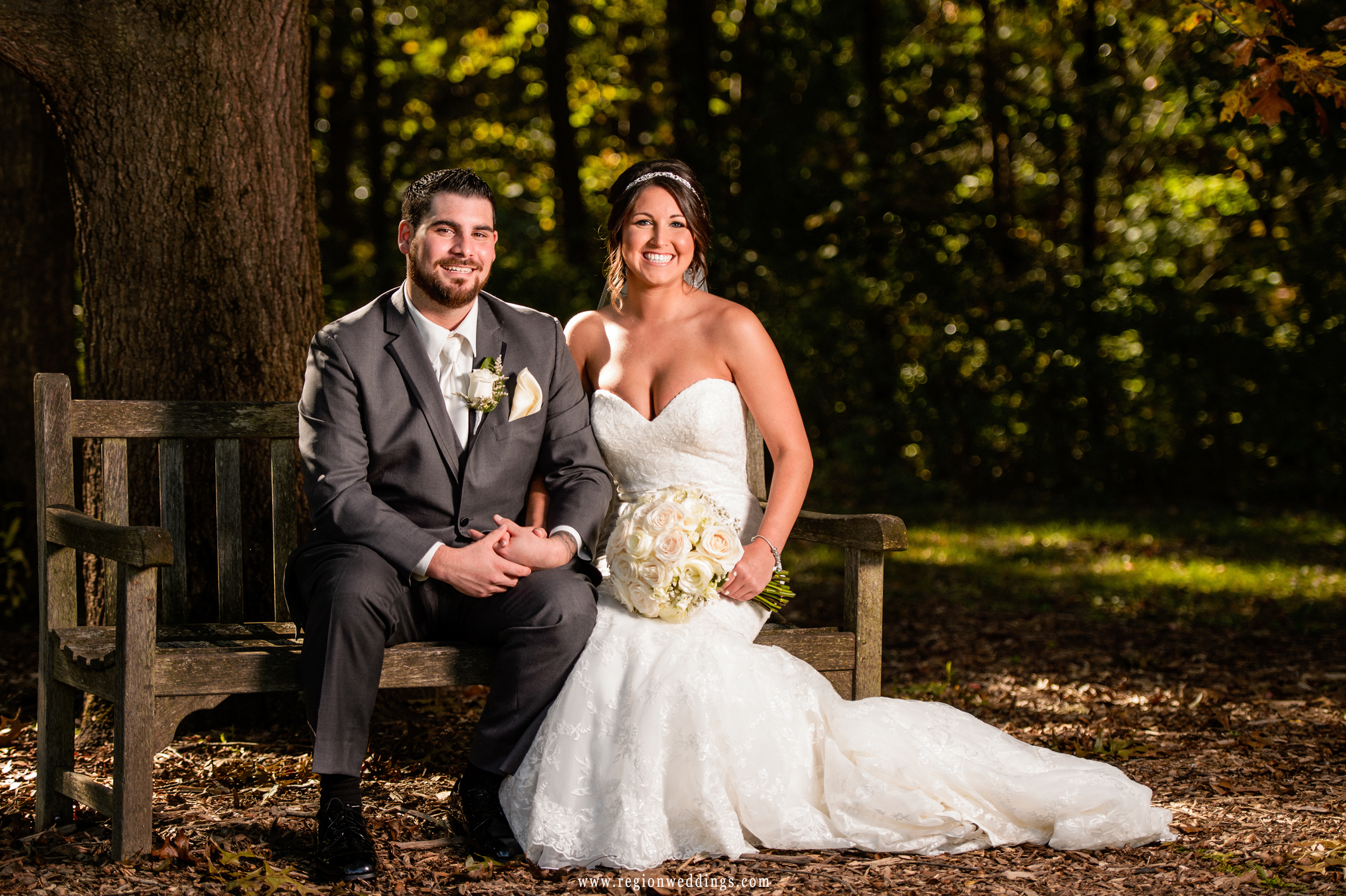 The bride and groom take a break on a bench at Taltree Arboretum.
