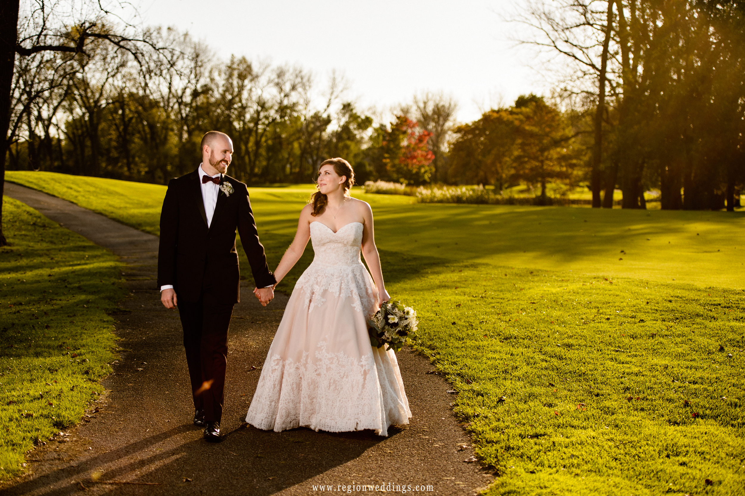 Bride and groom walk along a path at Briar Ridge Country Club golf course.