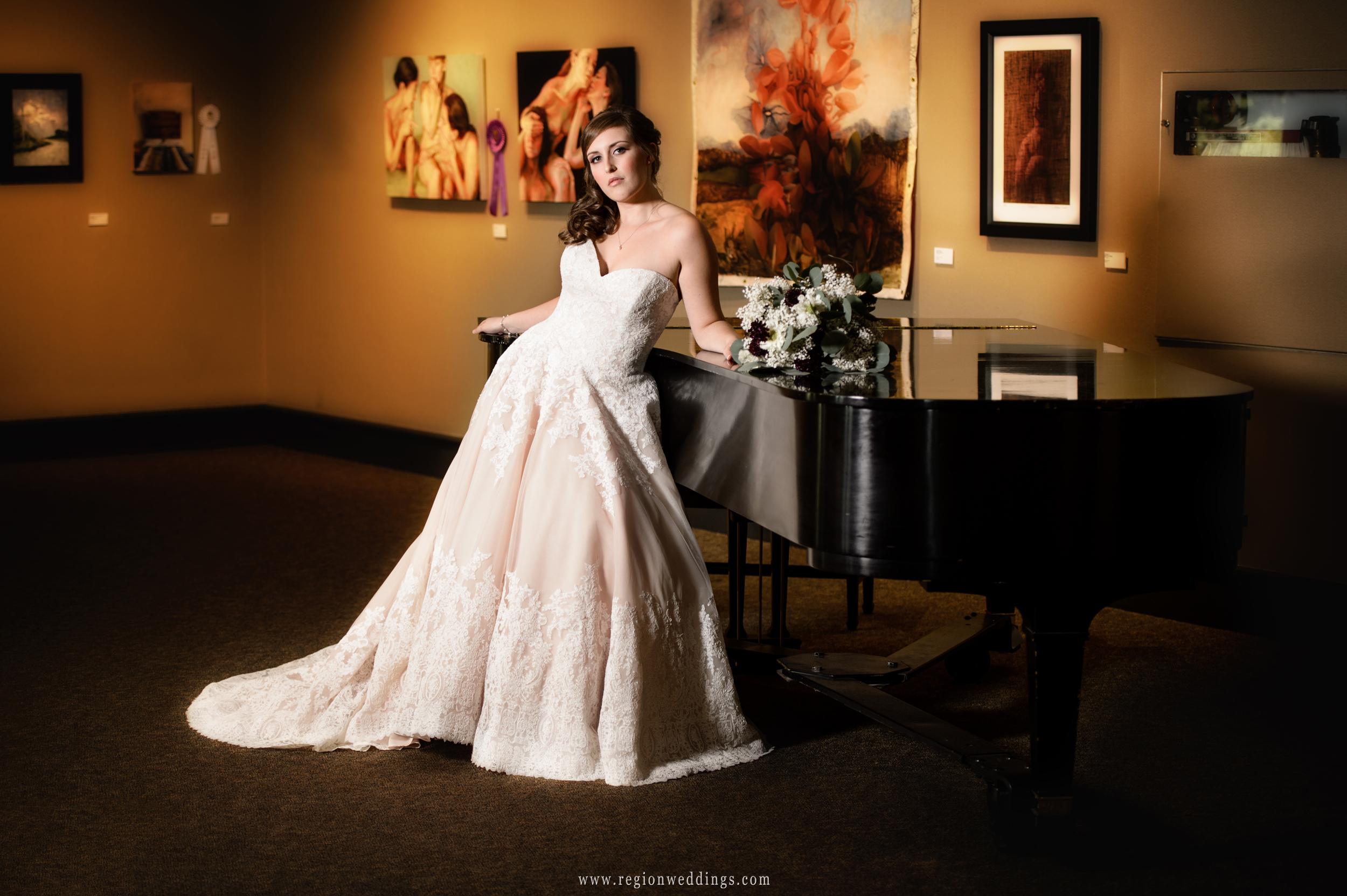 The bride rests against the piano at The Center For Visual and Performing Arts.