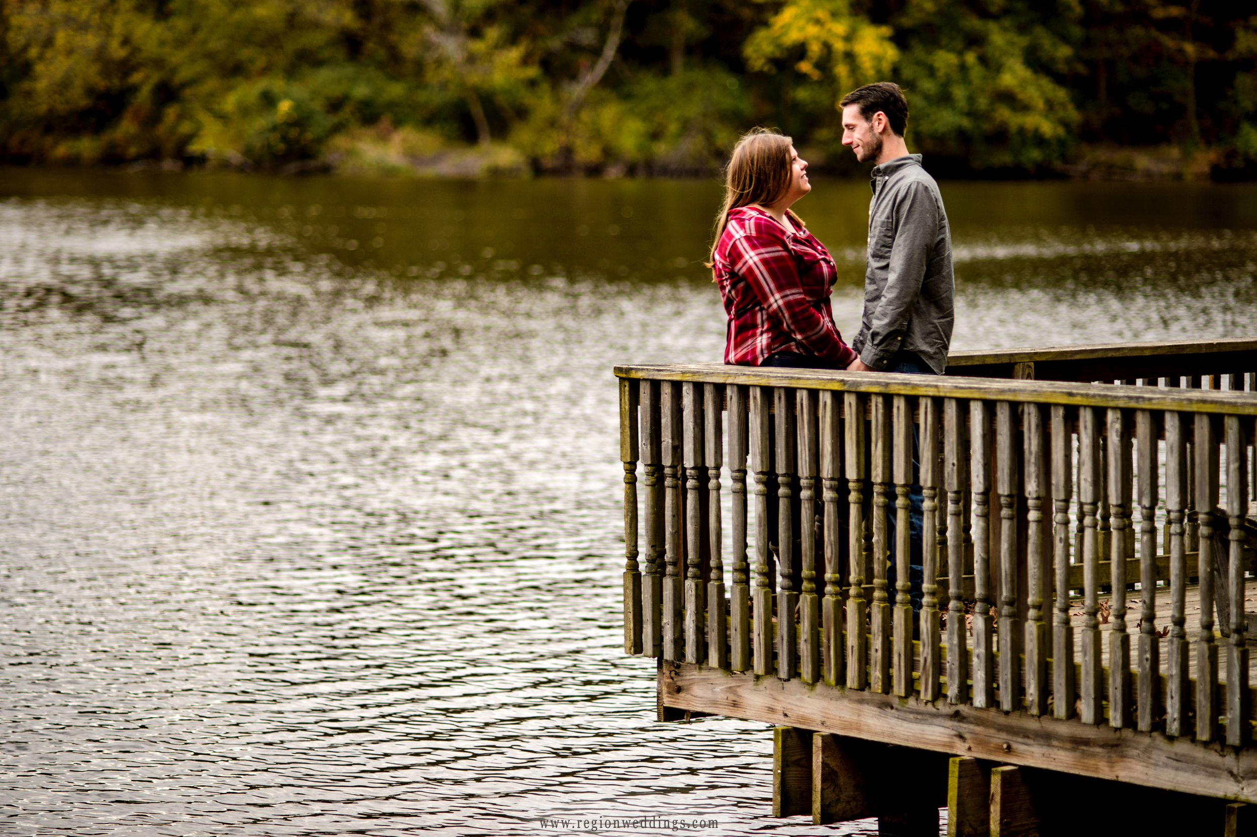 An engaged couple embraces at the edge of the pier at Lemon Lake County Park.
