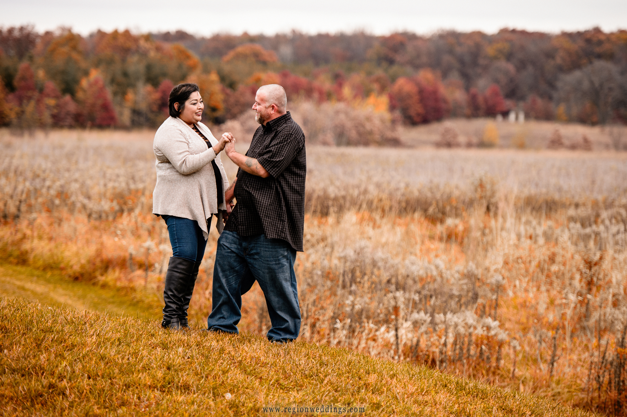 Fall engagement photo on the rolling hills at Taltree Arboretum.