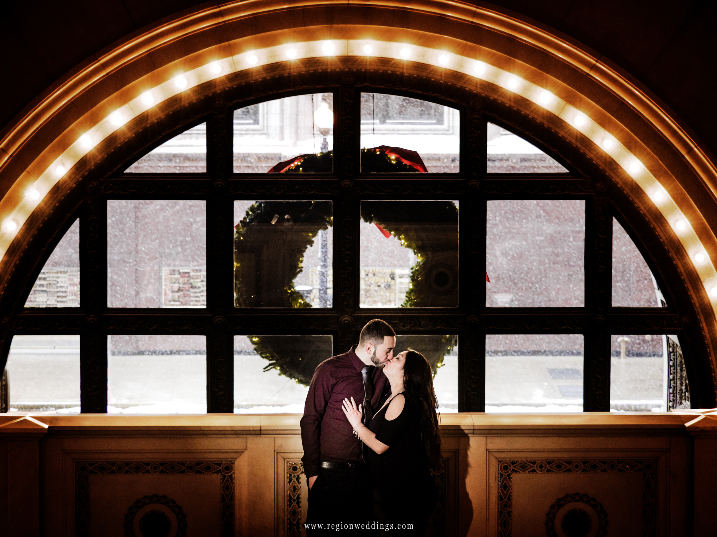 A newly engaged couple kisses by the lighted arch inside The Chicago Cultural Center.