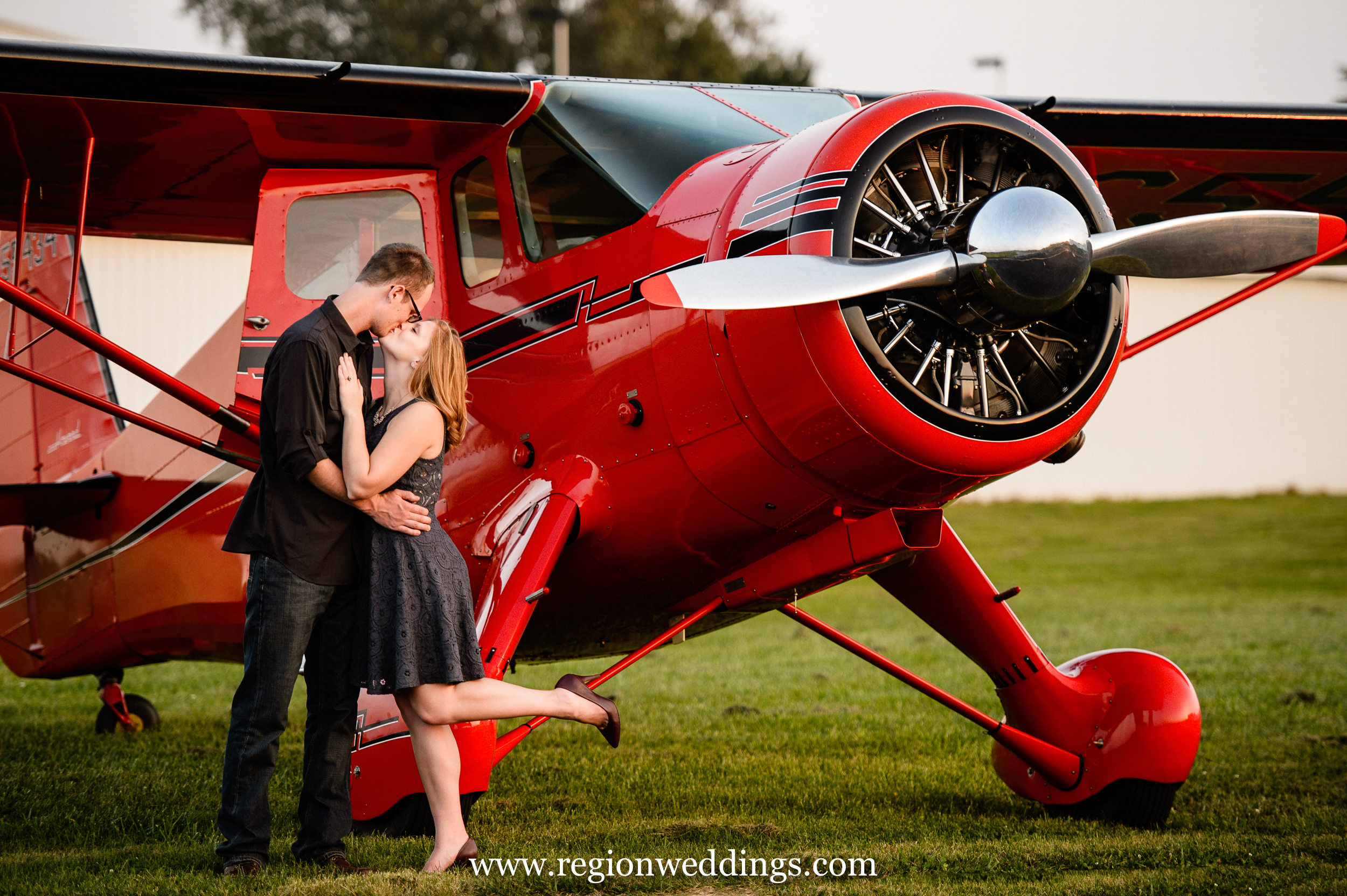 A couple shares a kiss next to a vintage airplane.