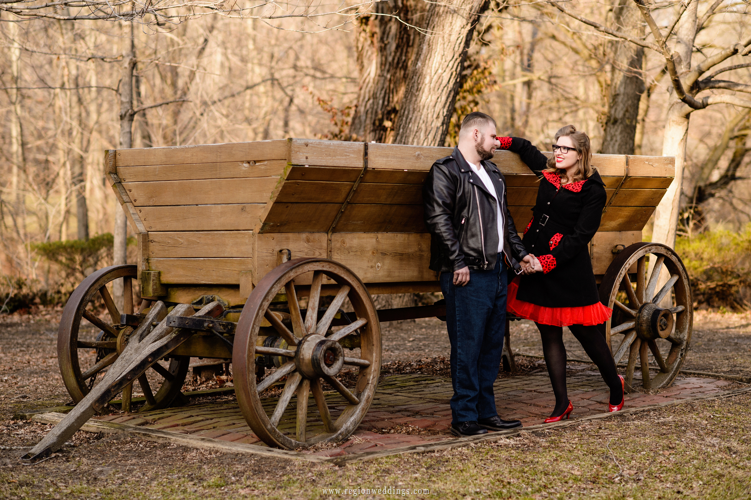 A young couple in front of a vintage wagon at Deep River County Park.
