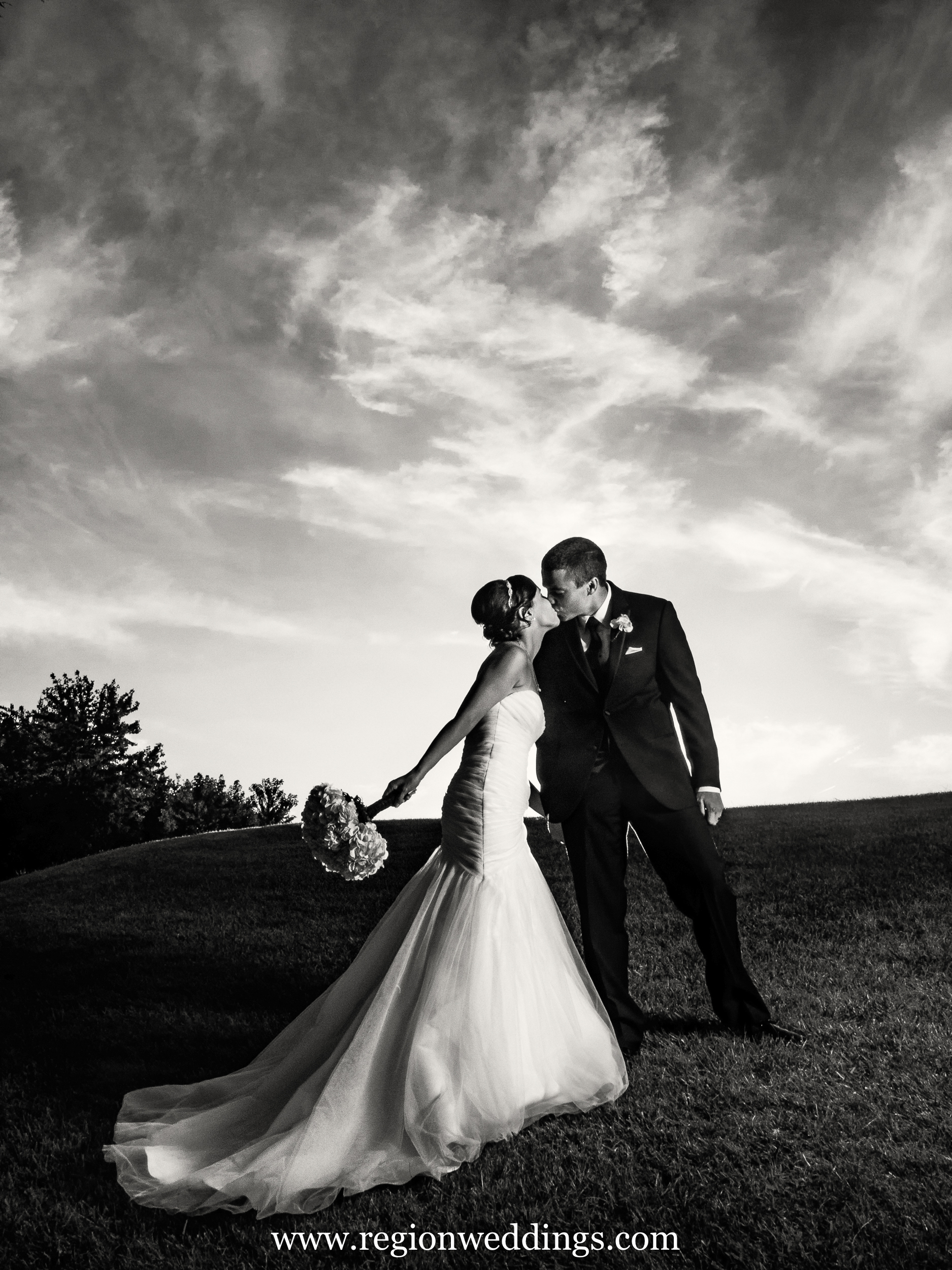 Black and white photo of bride and groom kissing on a hill at White Hawk Country Club.