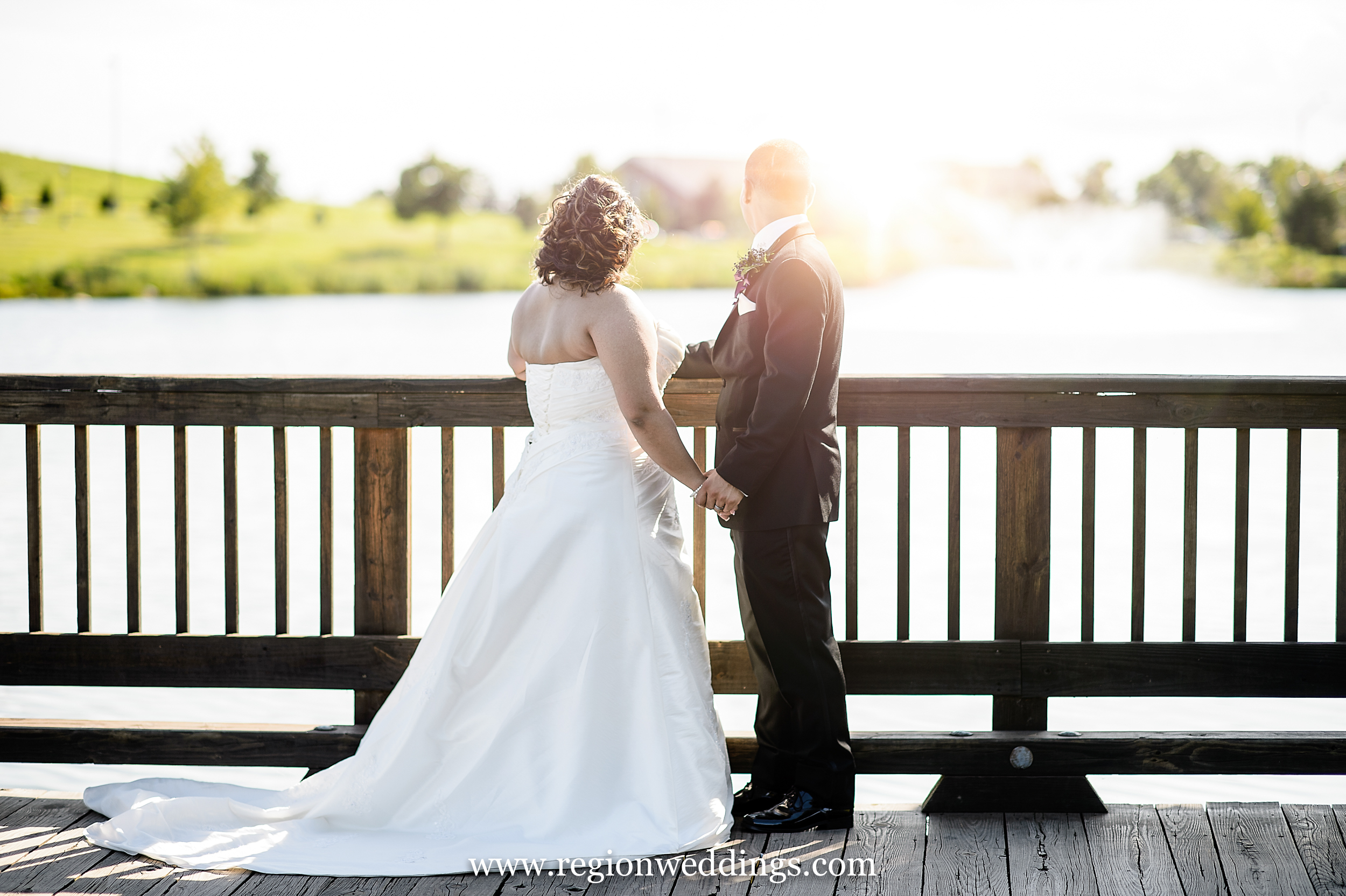 The bride and groom are illuminated by sun on the bridge at Centennial Park in Munster, Indiana.