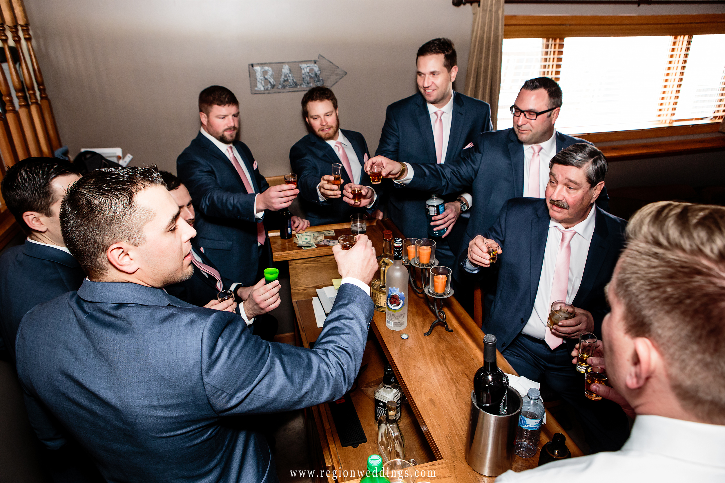 The groom and groomsmen toast to the big day ahead.