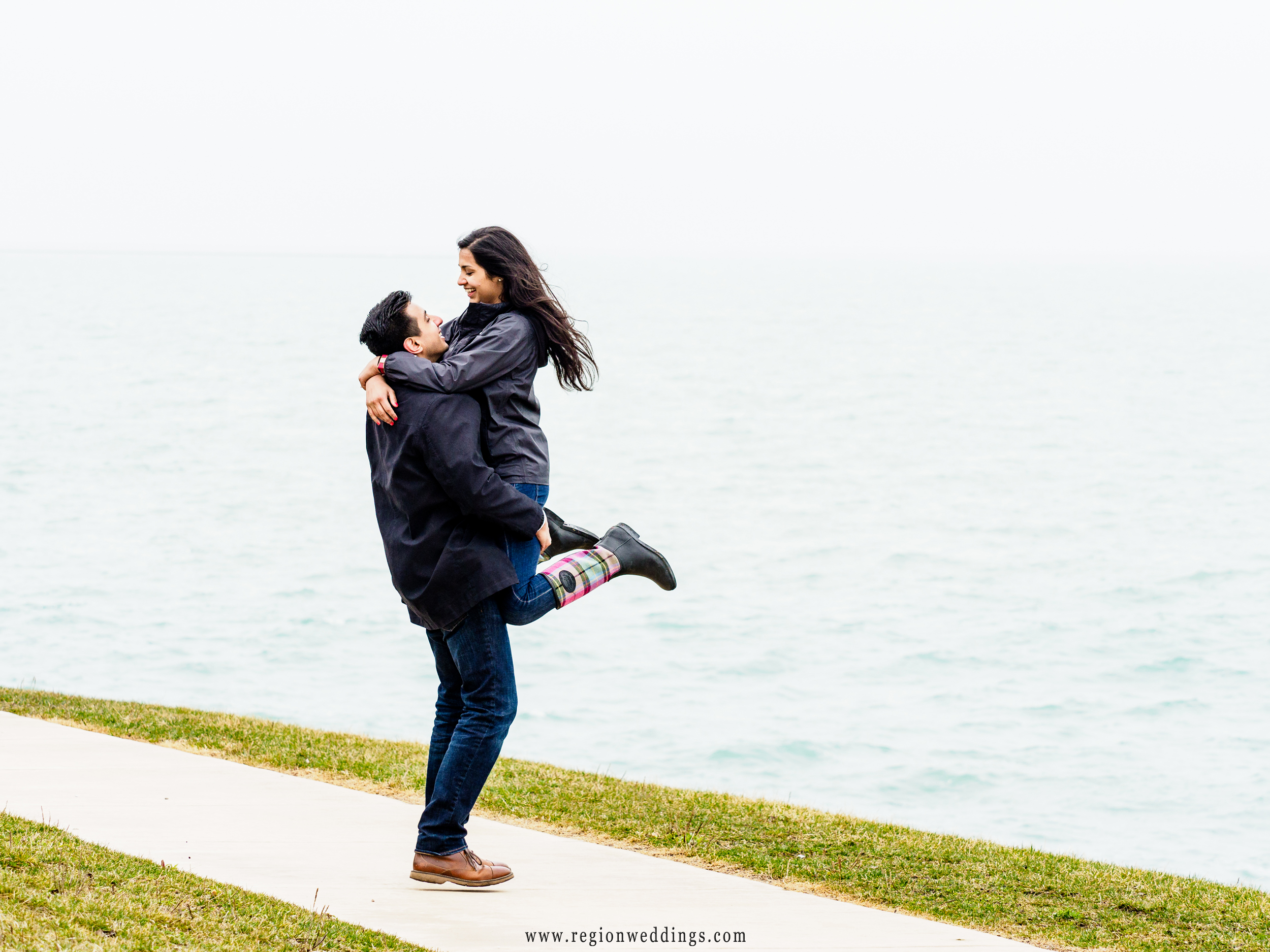 A newly engaged couple celebrates with Lake Michigan in the background in Chicago.