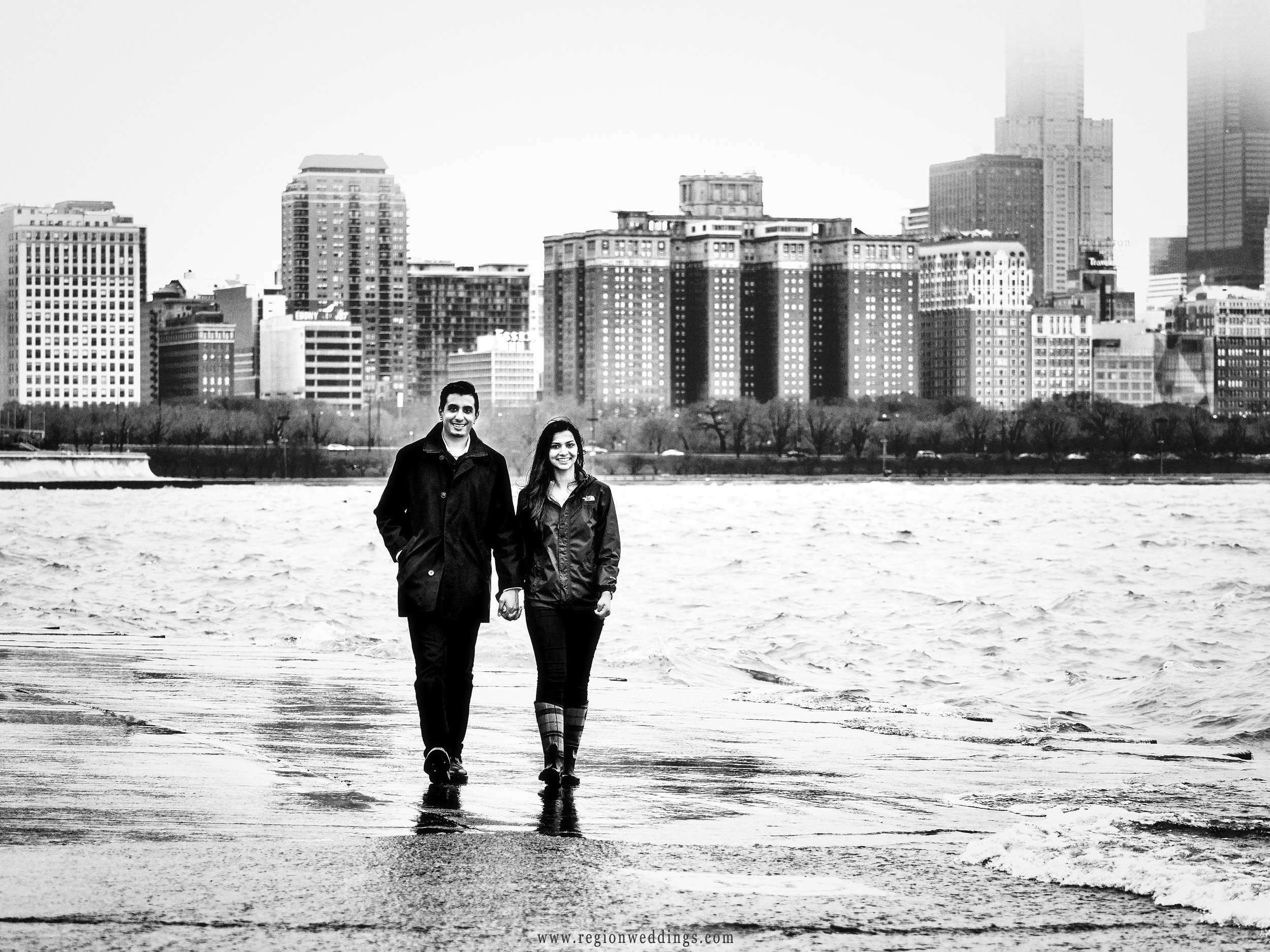A young couple walks along the shore of Lake Michigan in Chicago.