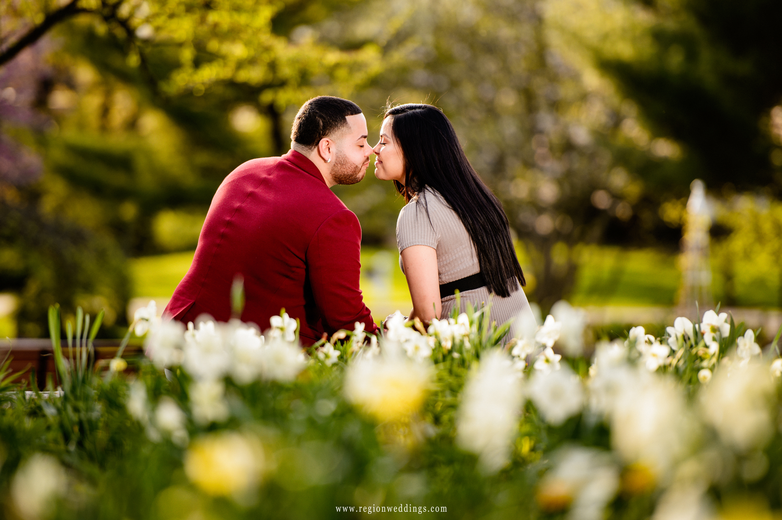 A young couple snuggles at Ogden Garden during their engagement session.