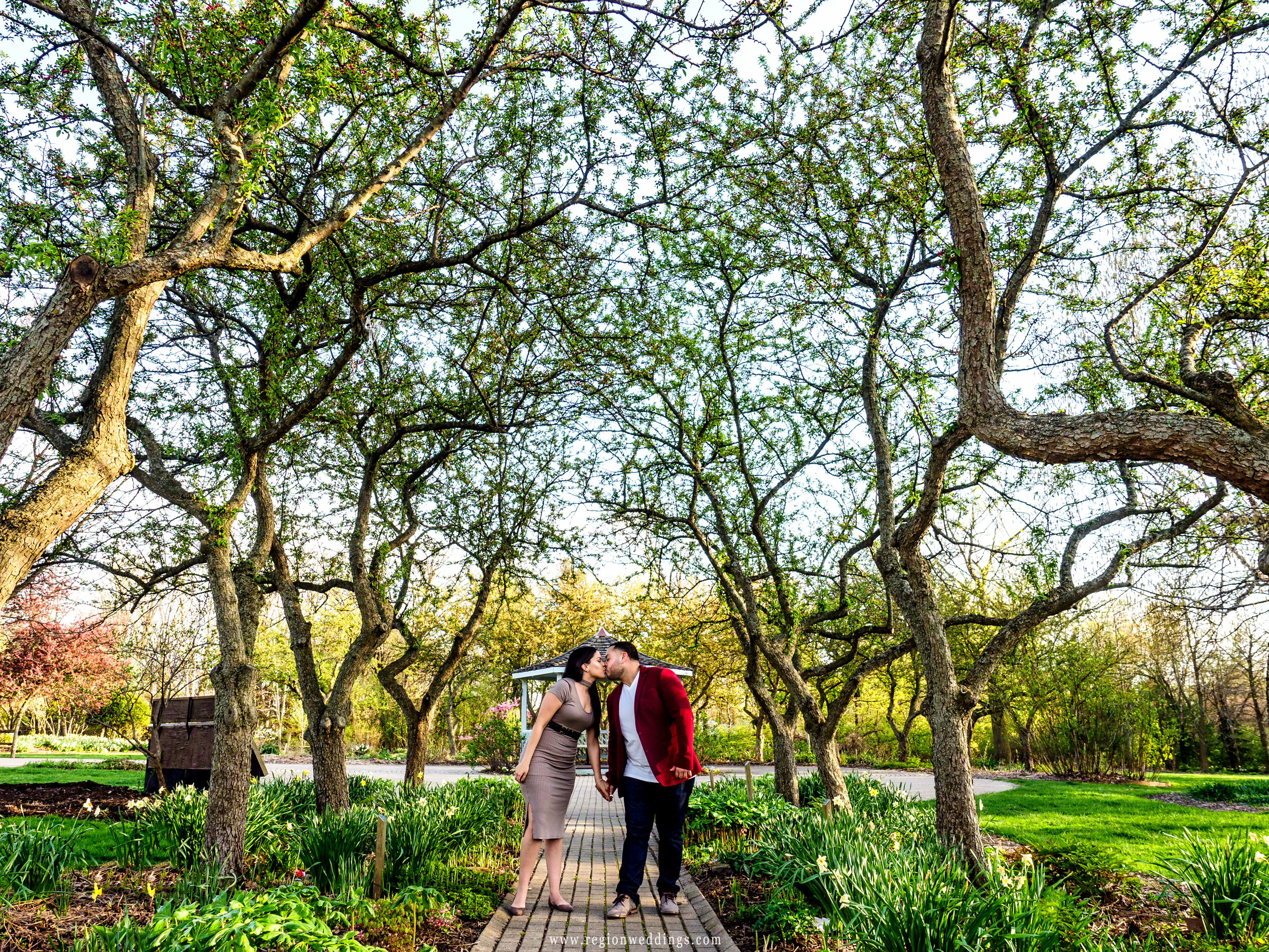 A couple kisses in front of the gazebo pathway at Ogden Garden.