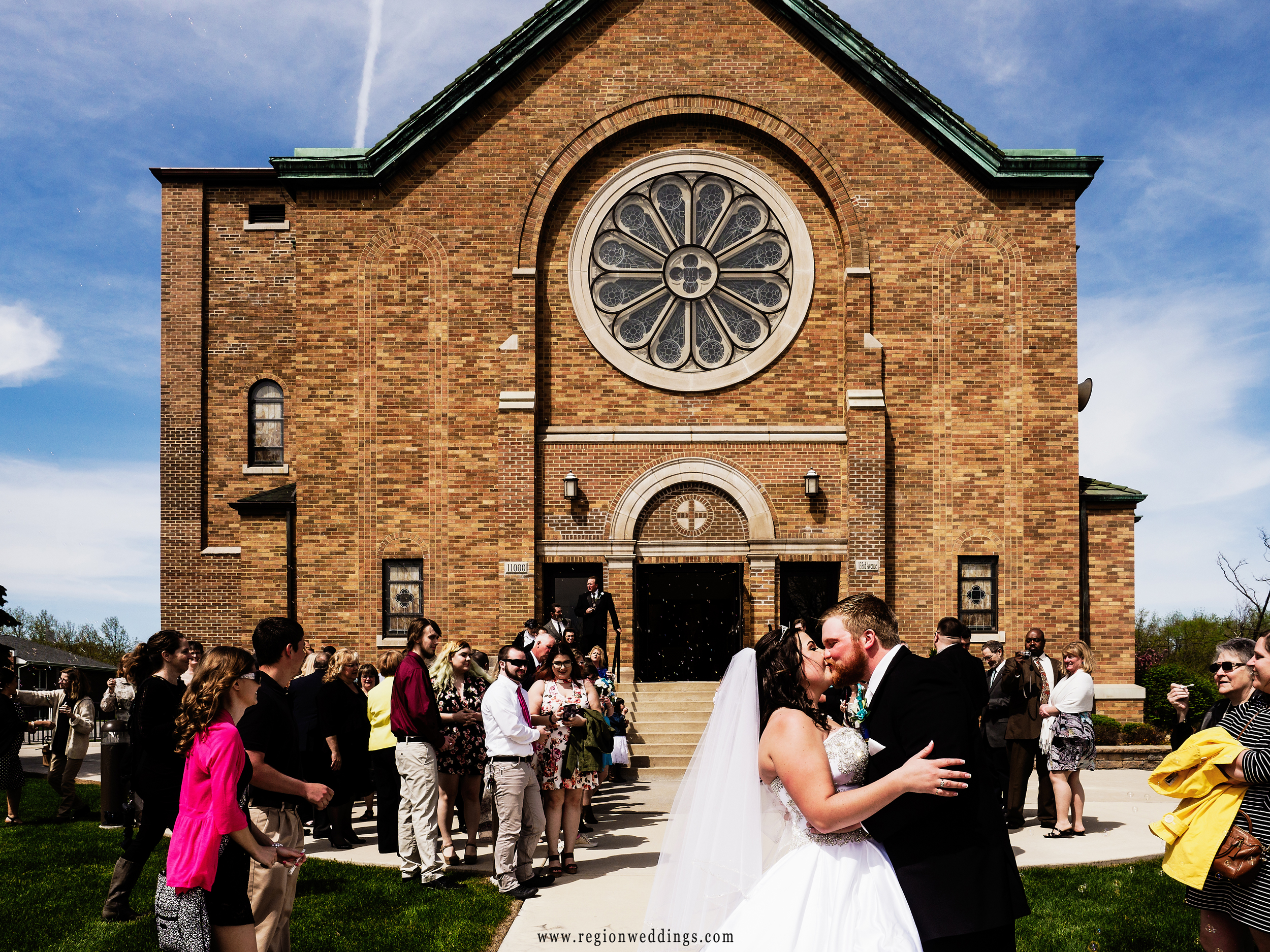 Bride and groom kiss amongst bubbles at Holy Name Catholic Church in Cedar Lake, Indiana.