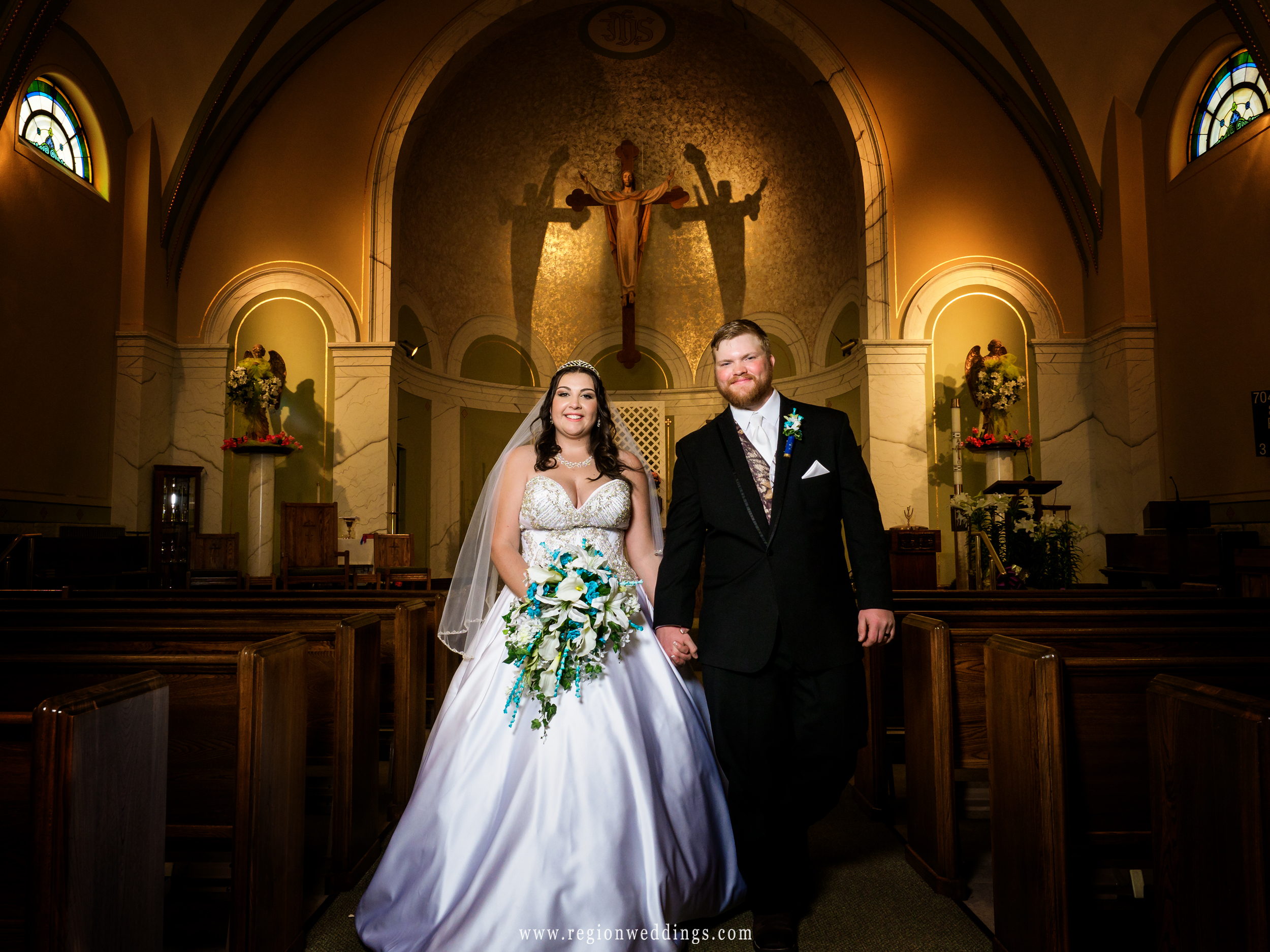 Bride and groom walk in the center aisle of church.