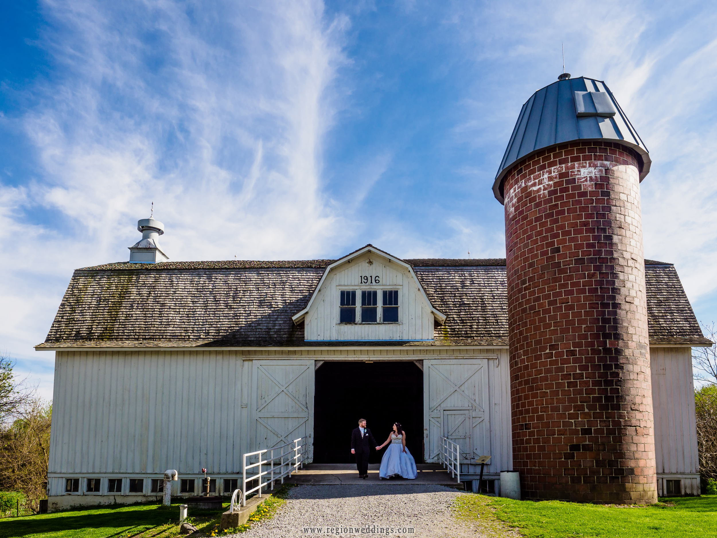 The bride and groom take a stroll at the Buckley Homestead barn in Lowell, Indiana.