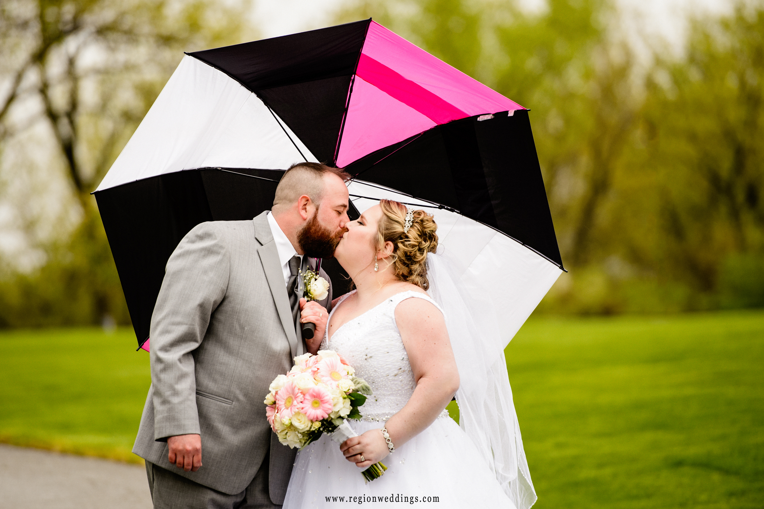 Bride and groom underneath a pink and black umbrella.