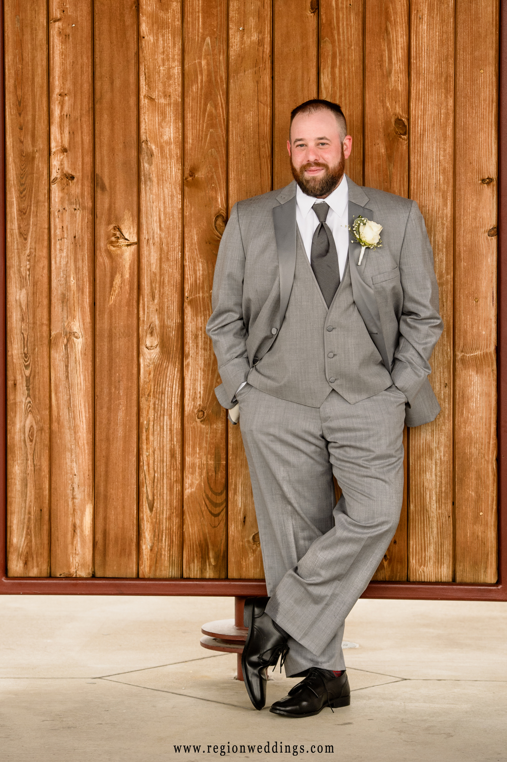 The groom leans against the wall of the amphitheater at Centennial Park.