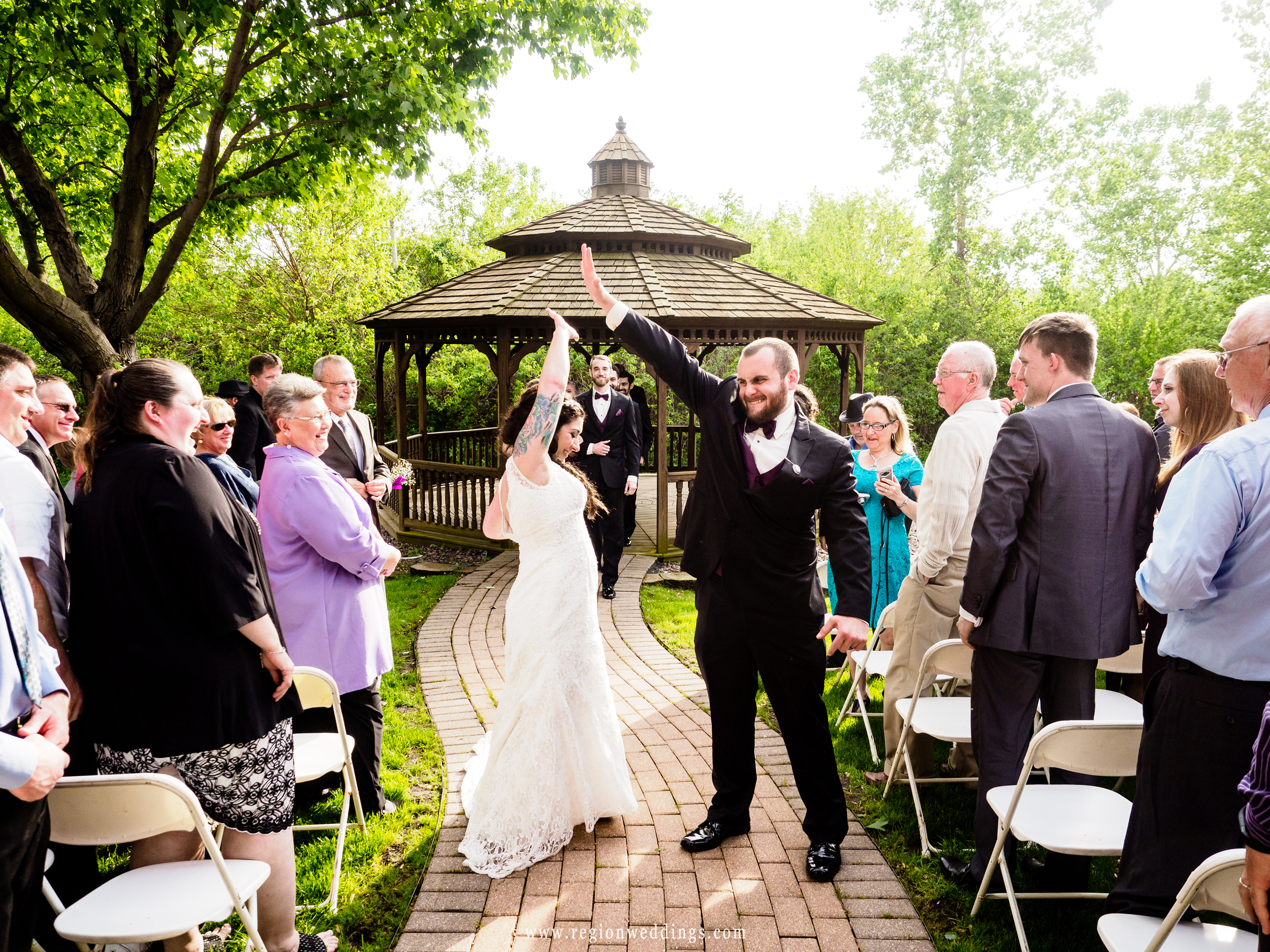 The bride and groom go for a high five as they exit the gazebo at Villa Cesare.