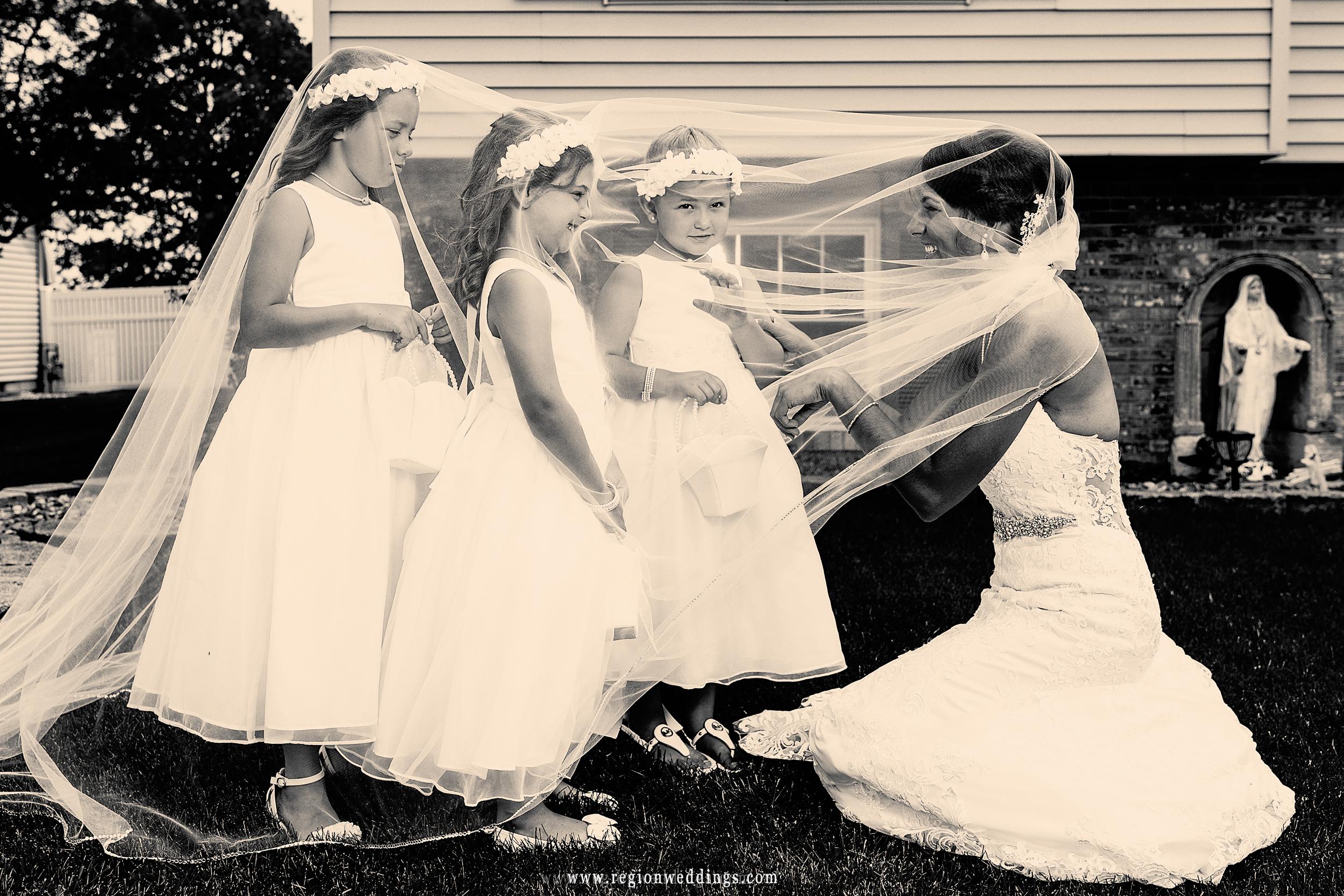 Flower girls hide underneath bride's veil.
