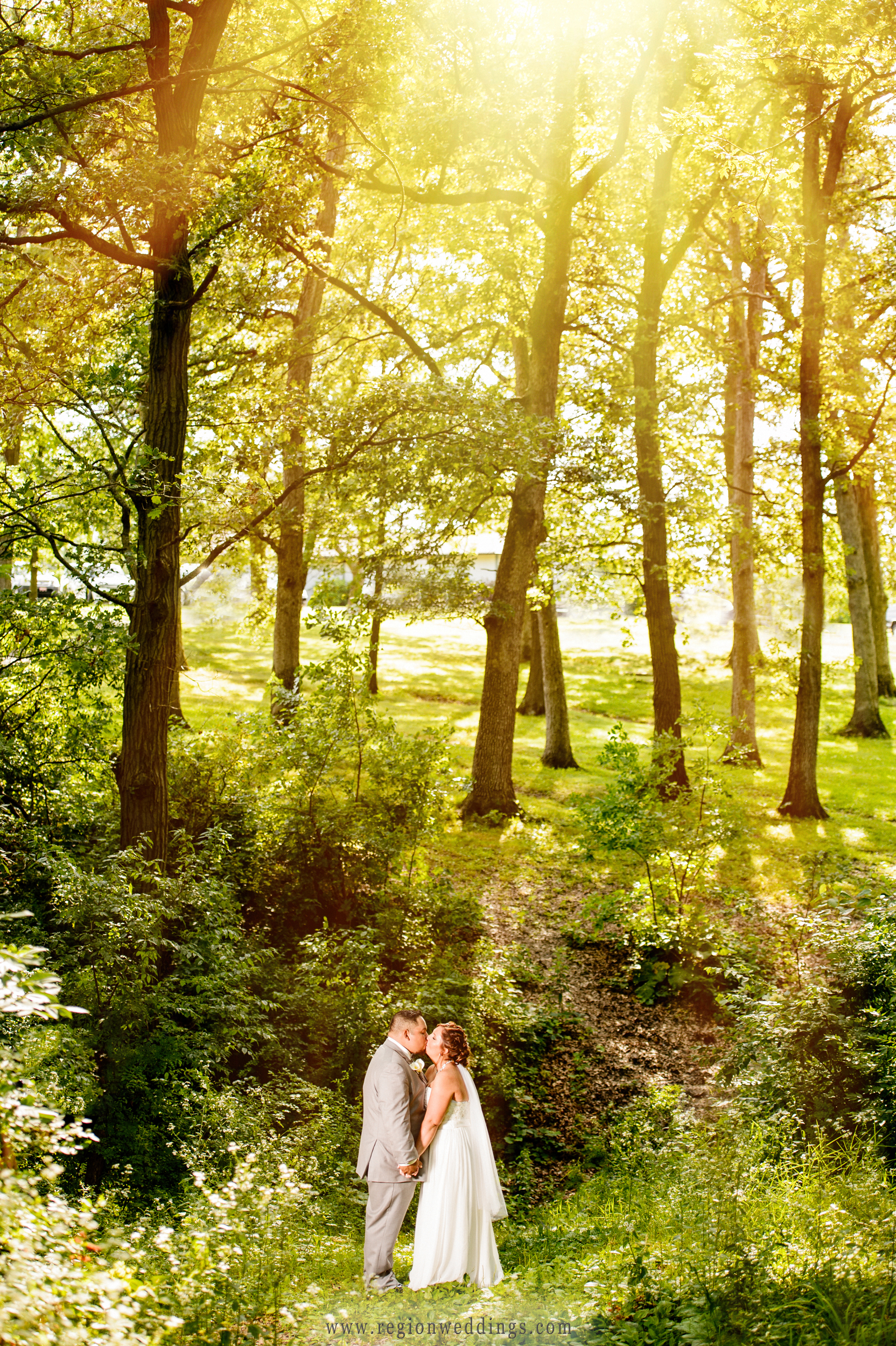 Rays of sun stream through the tall trees at Lemon Lake Park as the bride and groom kiss.