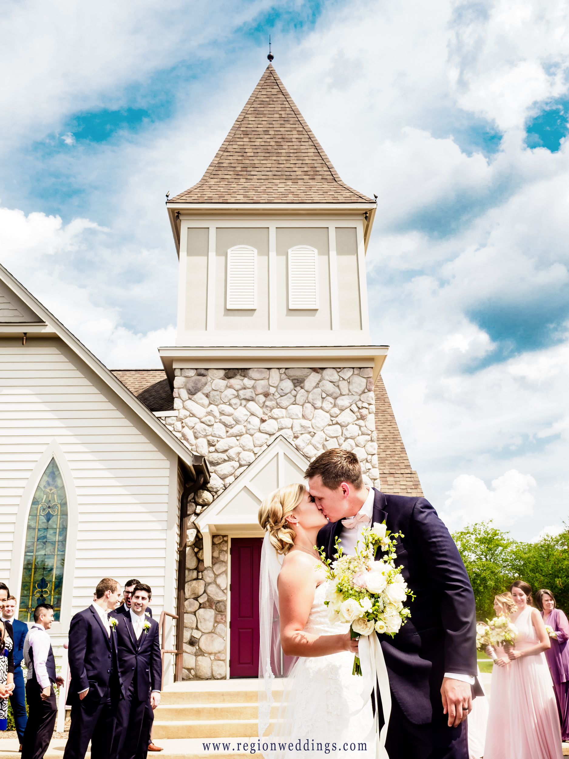The bride and groom kiss as they exit the Chapel at Aberdeen Manor.