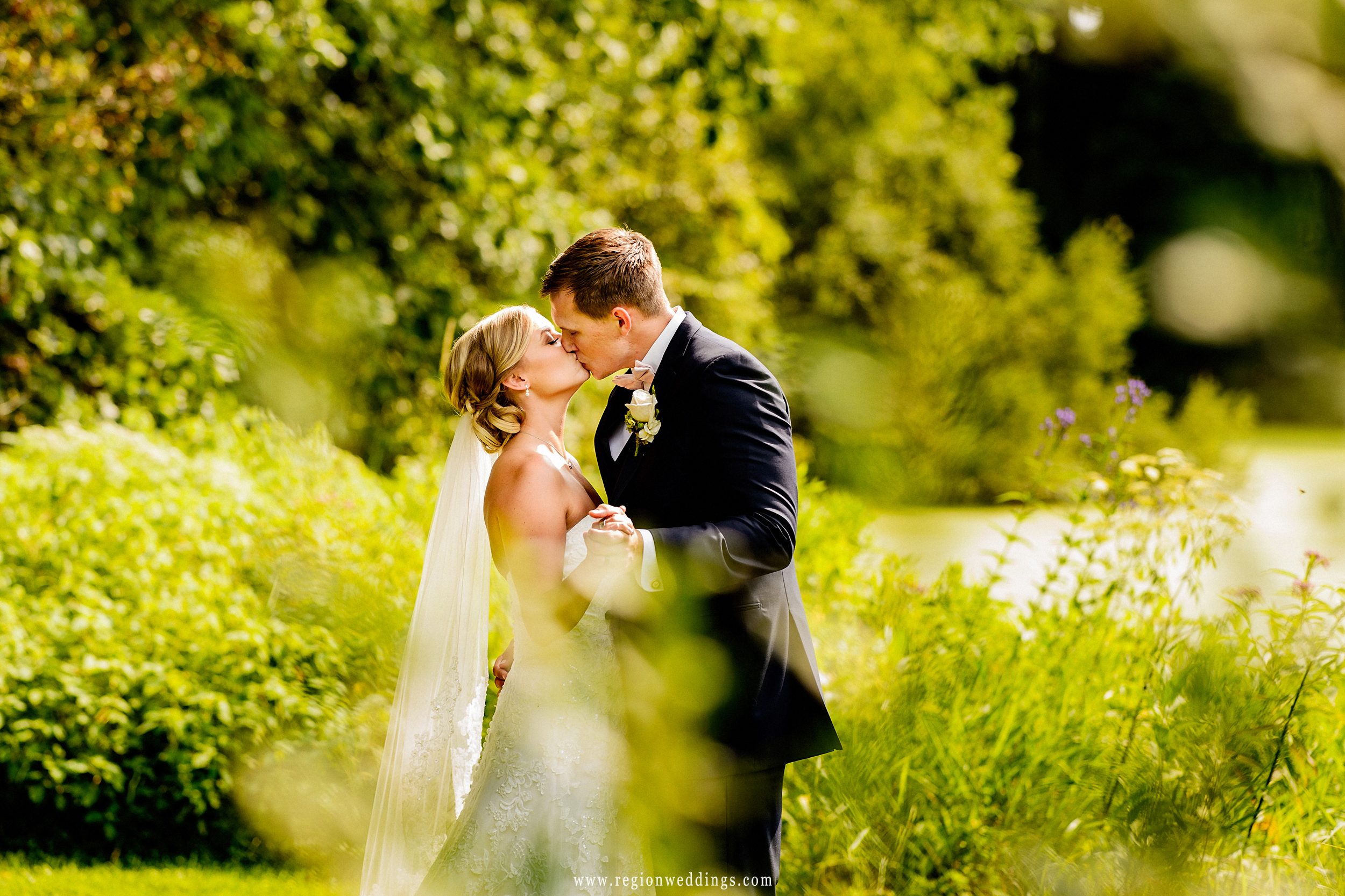 Bride and groom share in a kiss amidst the nature of Taltree Arboretum.