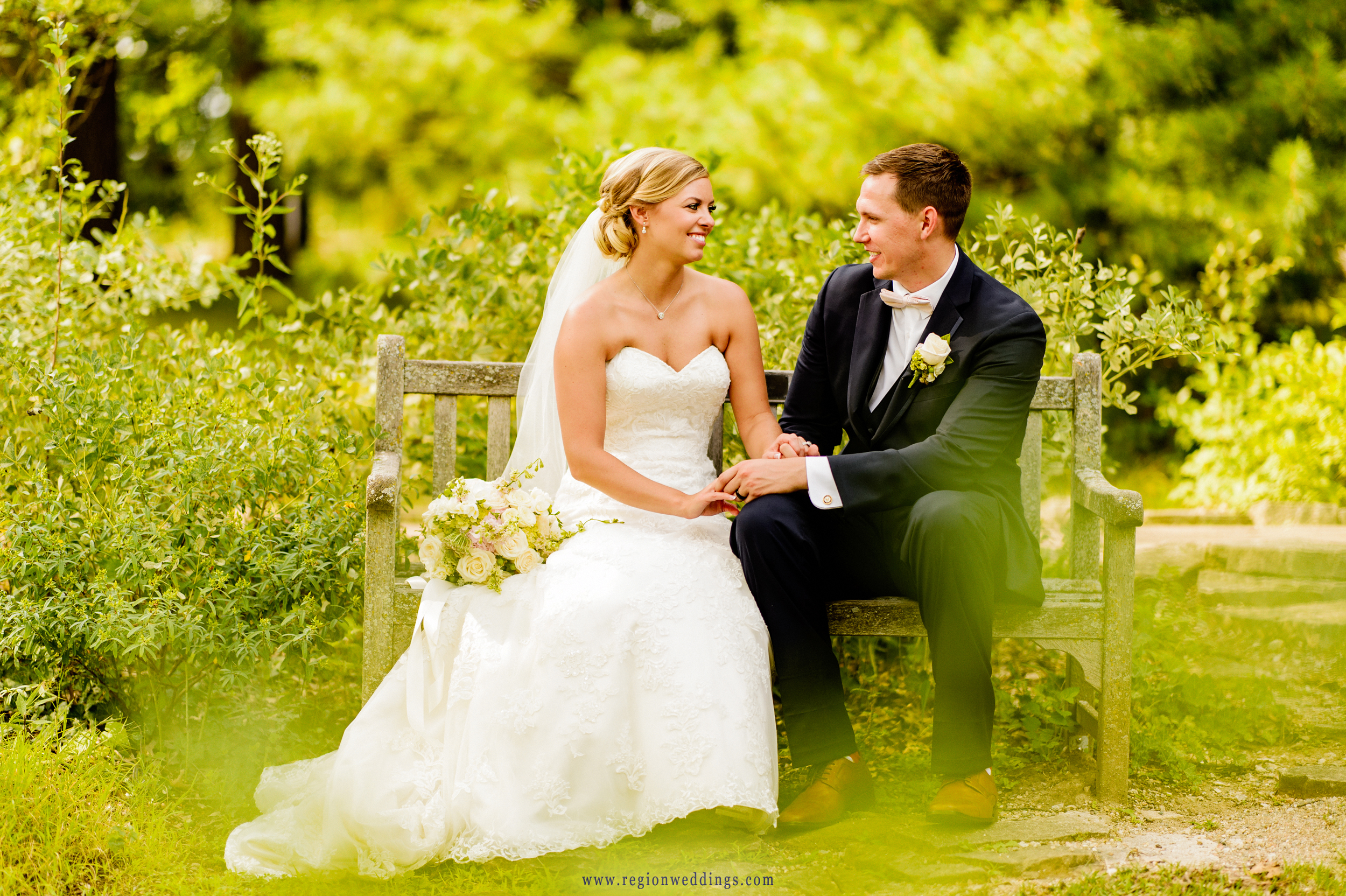 Bride and groom sit and chat on a bench surrounded by greenery at Taltree Arboretum.