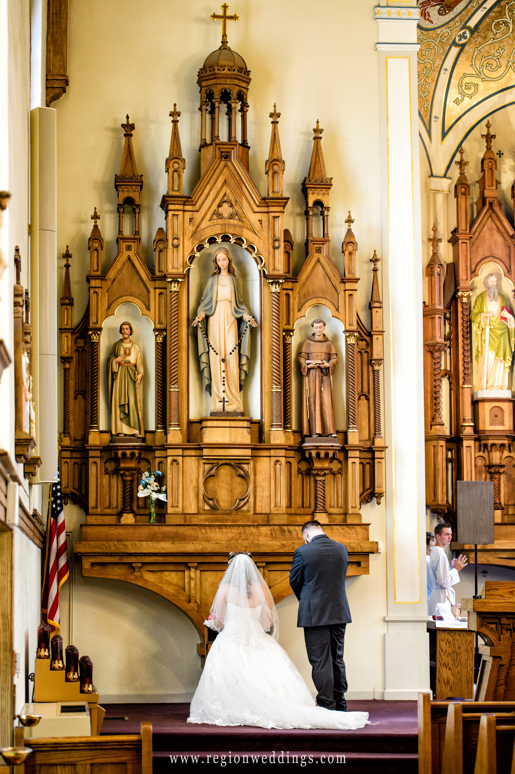 Bride and groom pray in front of the statue of Mary.
