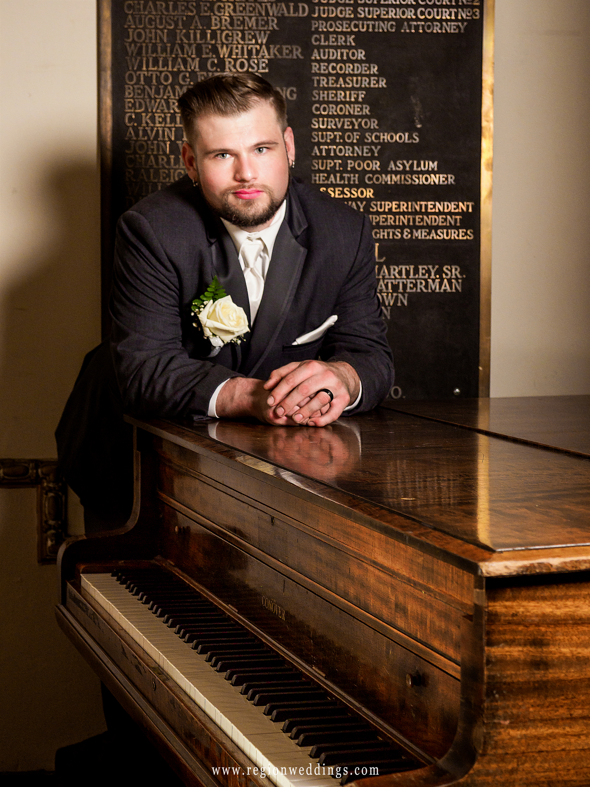The groom relaxes next to the vintage piano at The Halls of Justice.