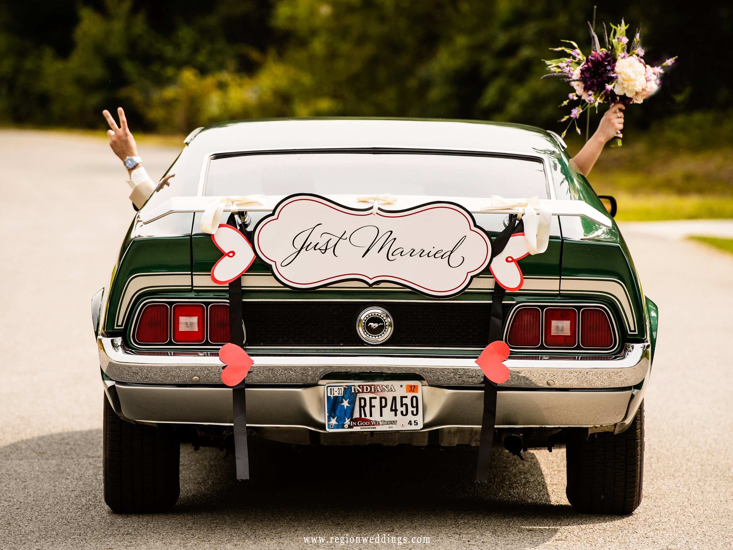 Bride and groom getaway drive in a classic Ford Mustang.