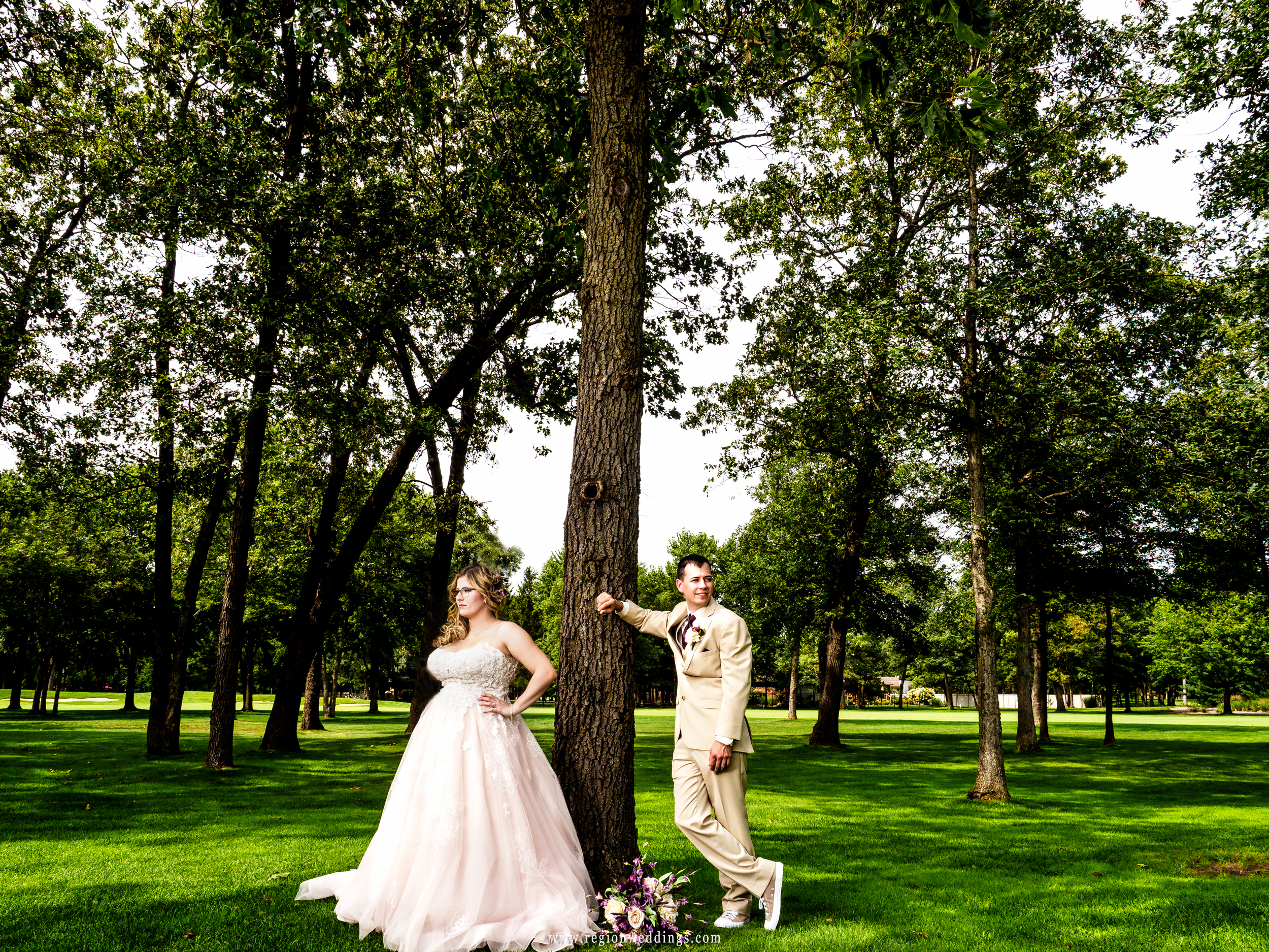 Bride and groom looking fashionable underneath the tall trees at Sandy Pines Pavilion.
