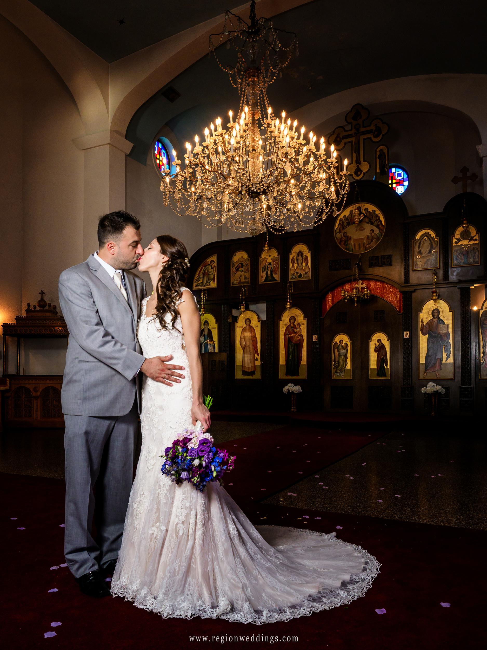 Bride and groom kiss at St. Simeon Serbian Orthodox Church.