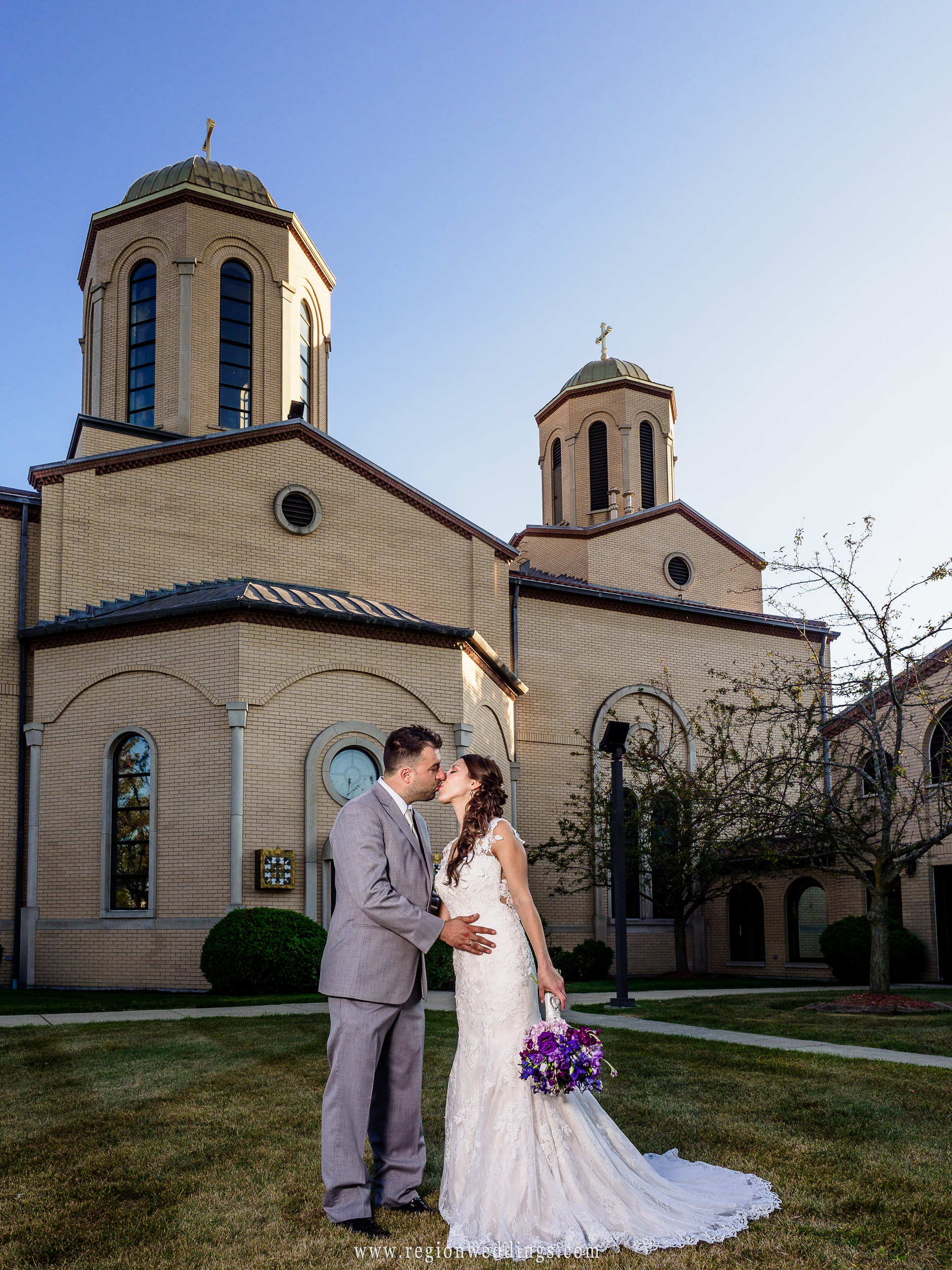 Bride and groom kiss in front of church in Lansing, Illinois.