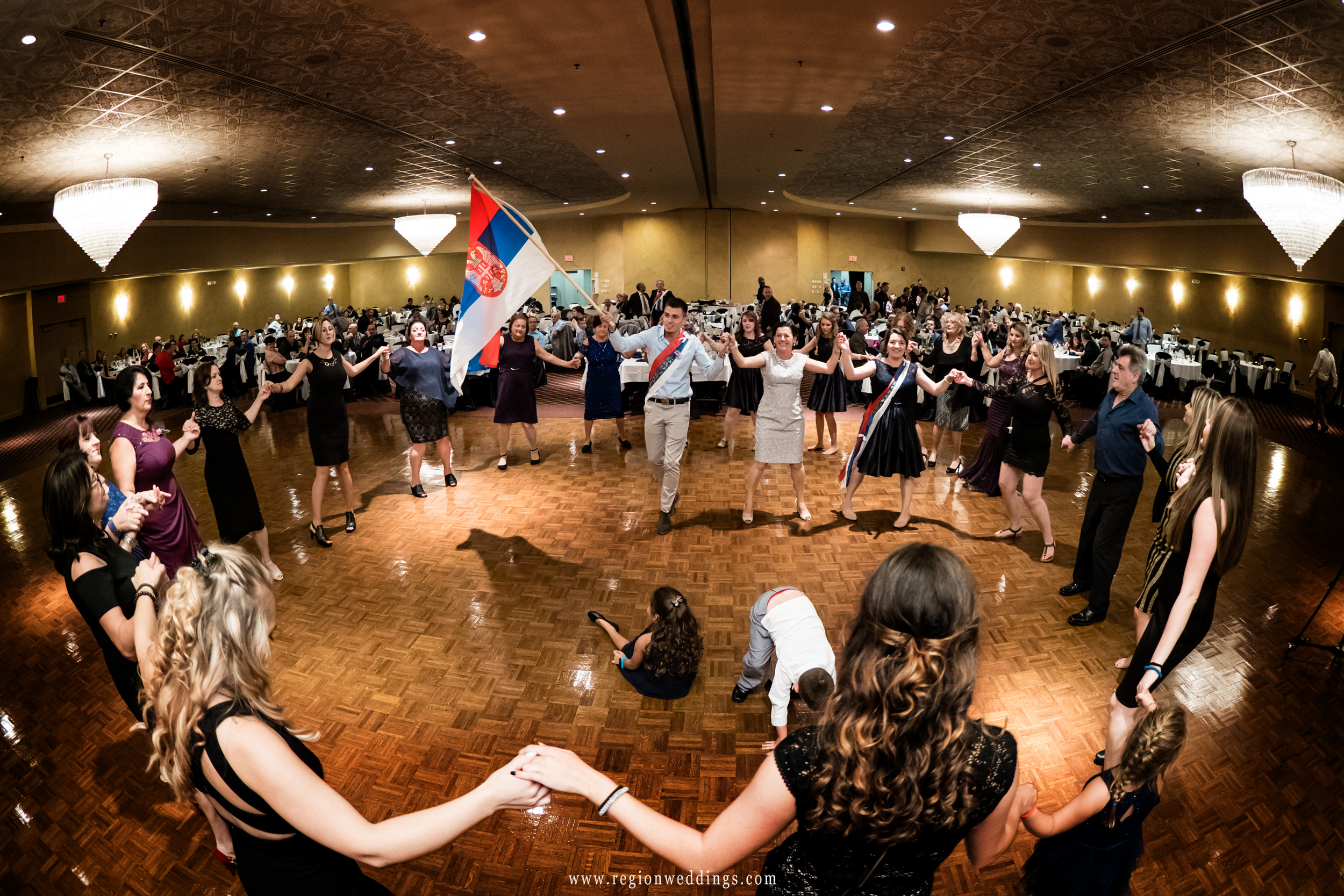 Family and friends dance in a circle to celebrate the bride and groom at the Serbian Social Center.