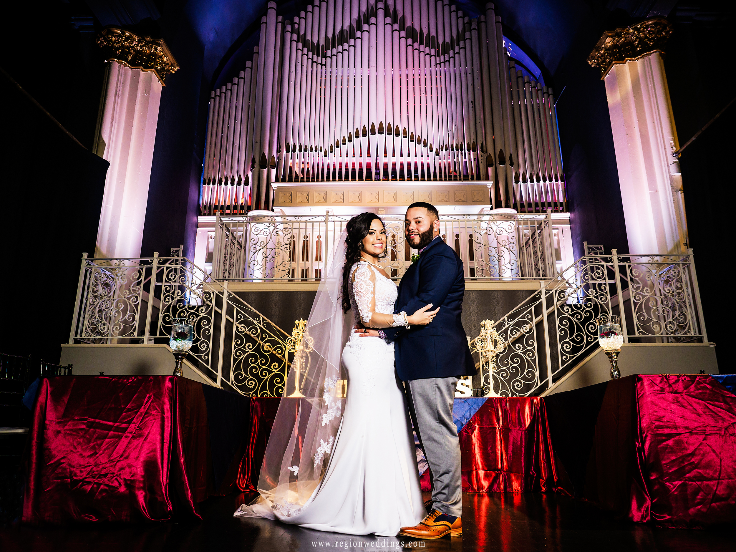 Bride and groom on stage inside Uptown Center ballroom.