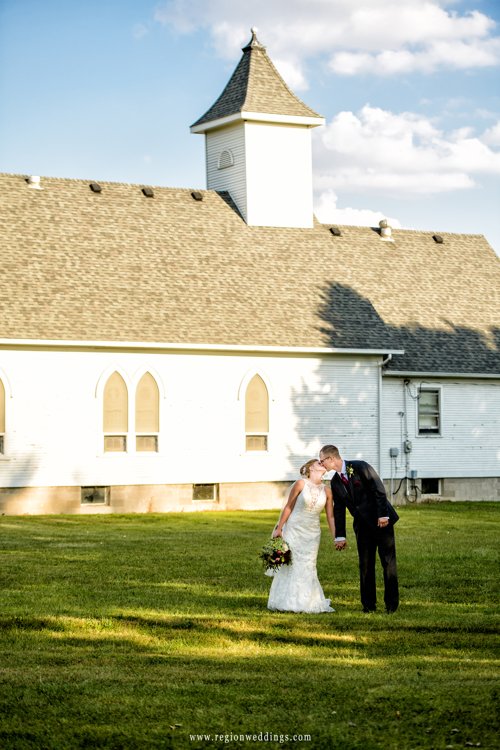 Church steeple in the background as the bride and groom kiss.