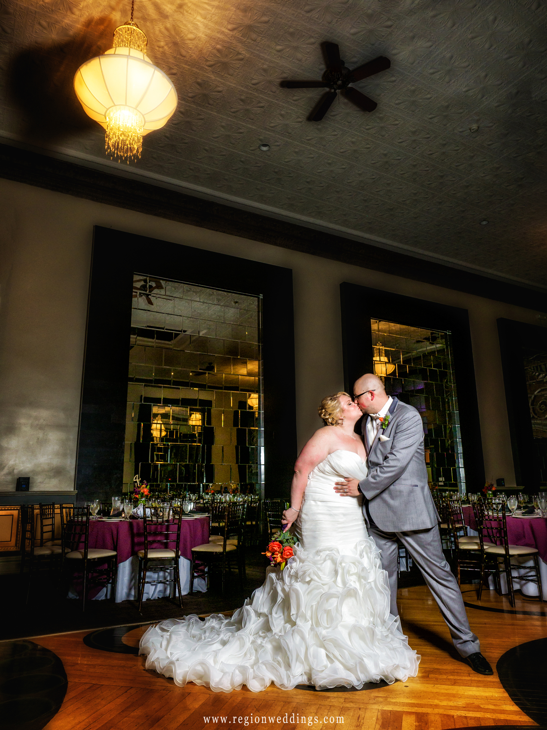 Bride and groom share a kiss in the middle of the ballroom of The Allure.