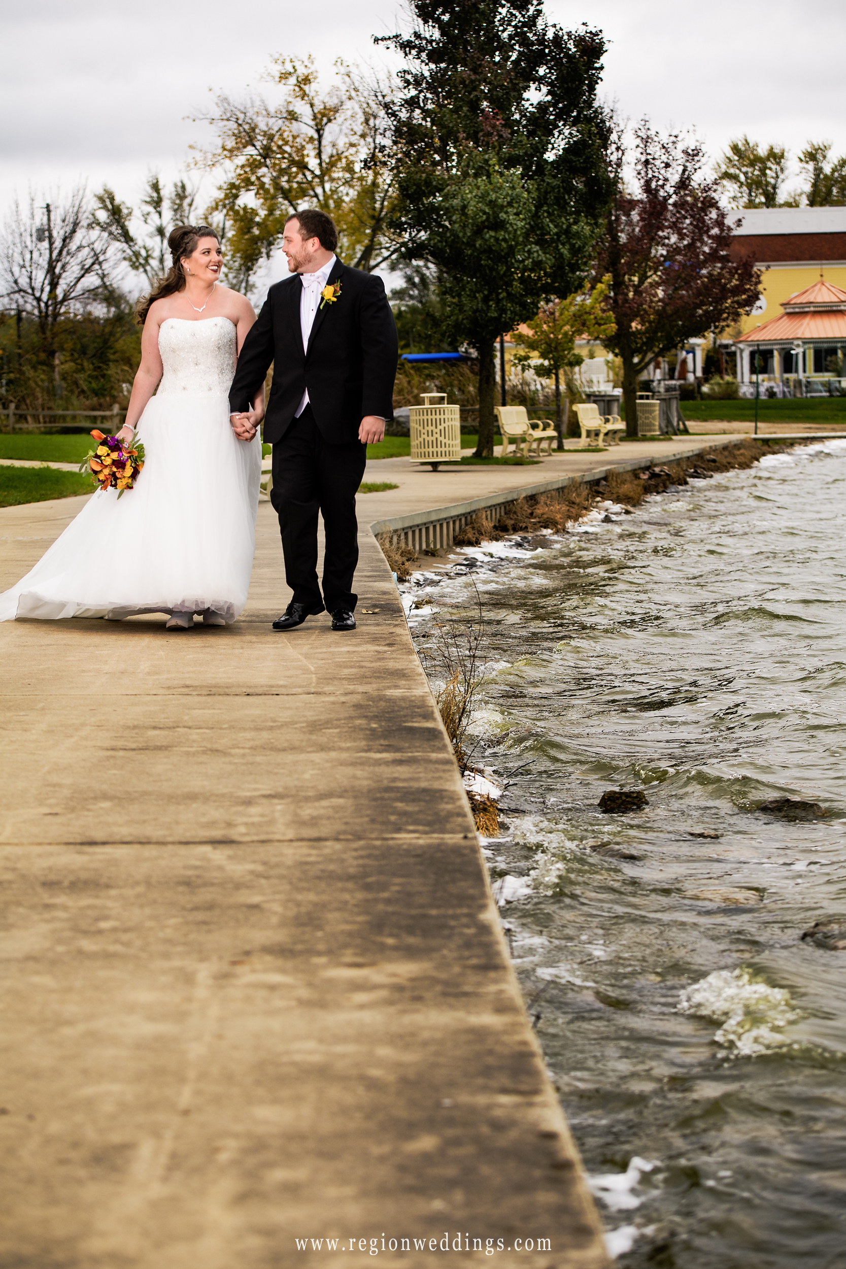 Bride and groom take a walk along the boardwalk of Cedar Lake.