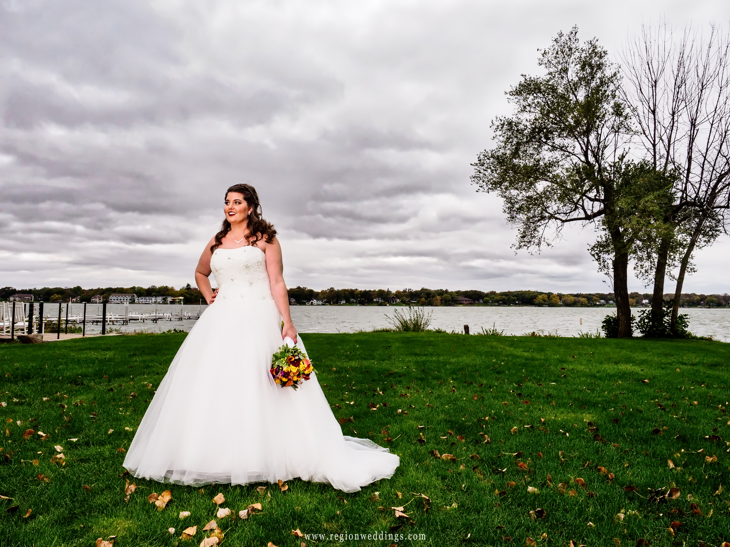 The bride lakeside with storm clouds on the horizon.