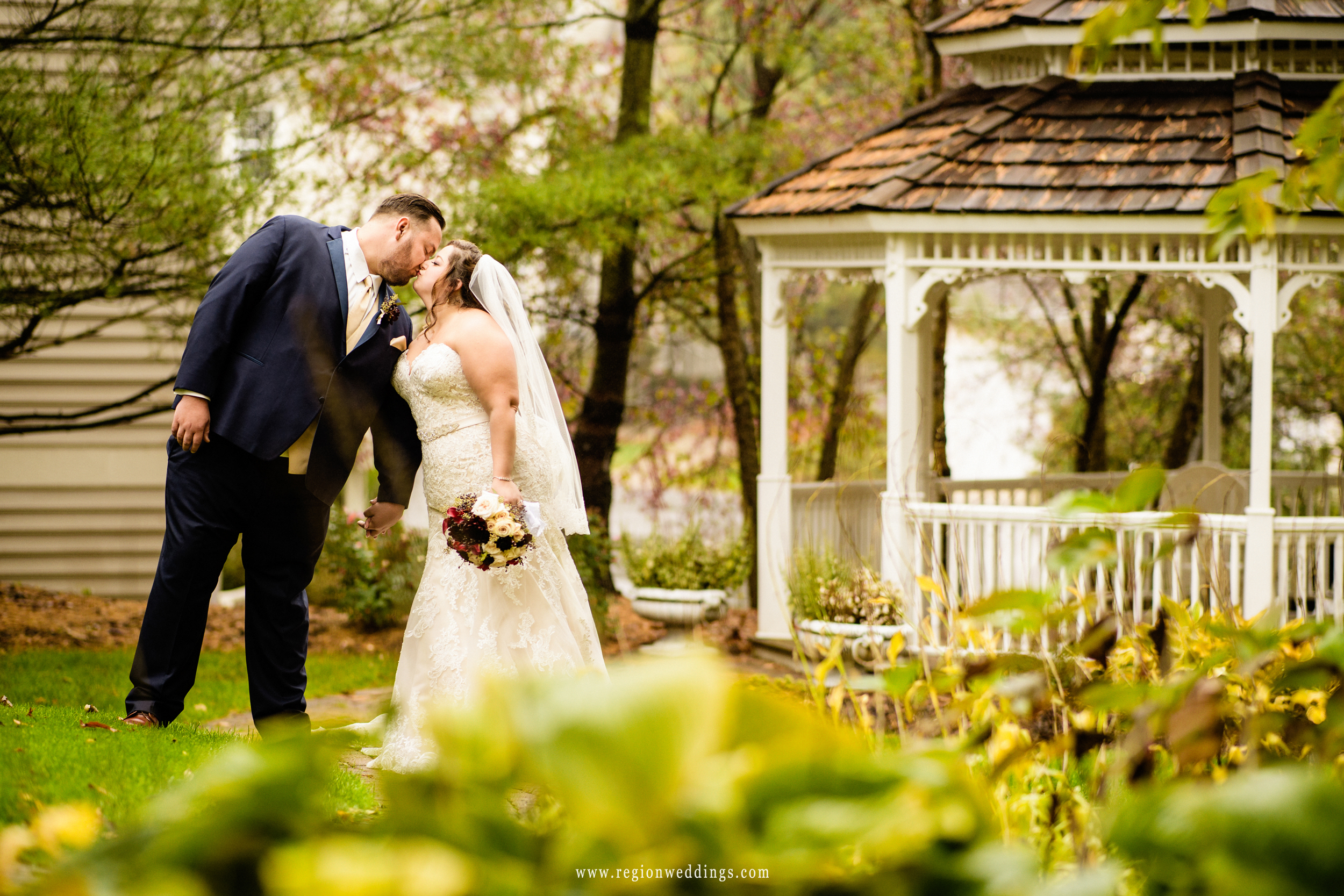 Bride and groom kiss in front of the gazebo at inn of Aberdeen.