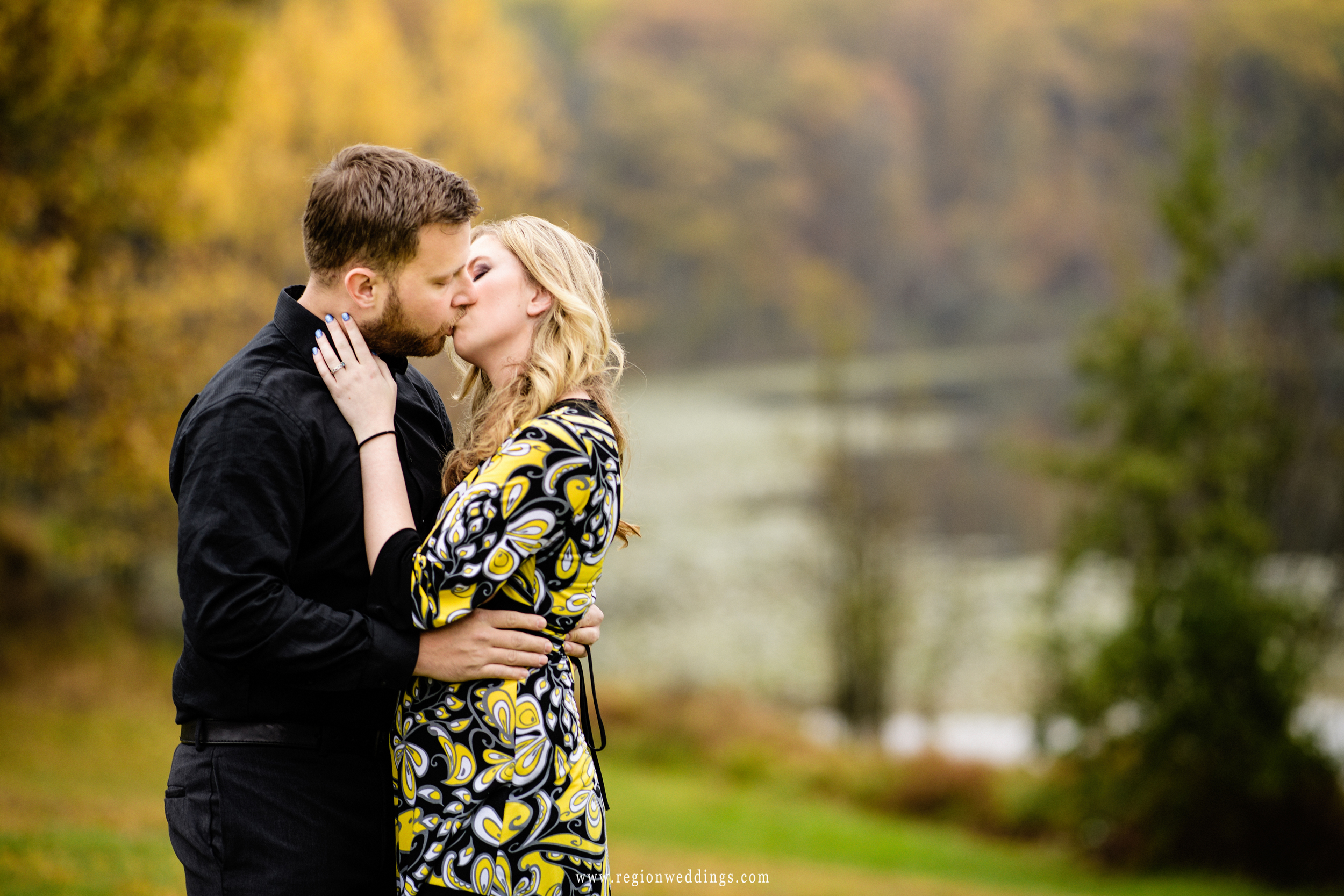 Yellow leaves fade into the background as a young couple kisses for their Fall engagement photo.