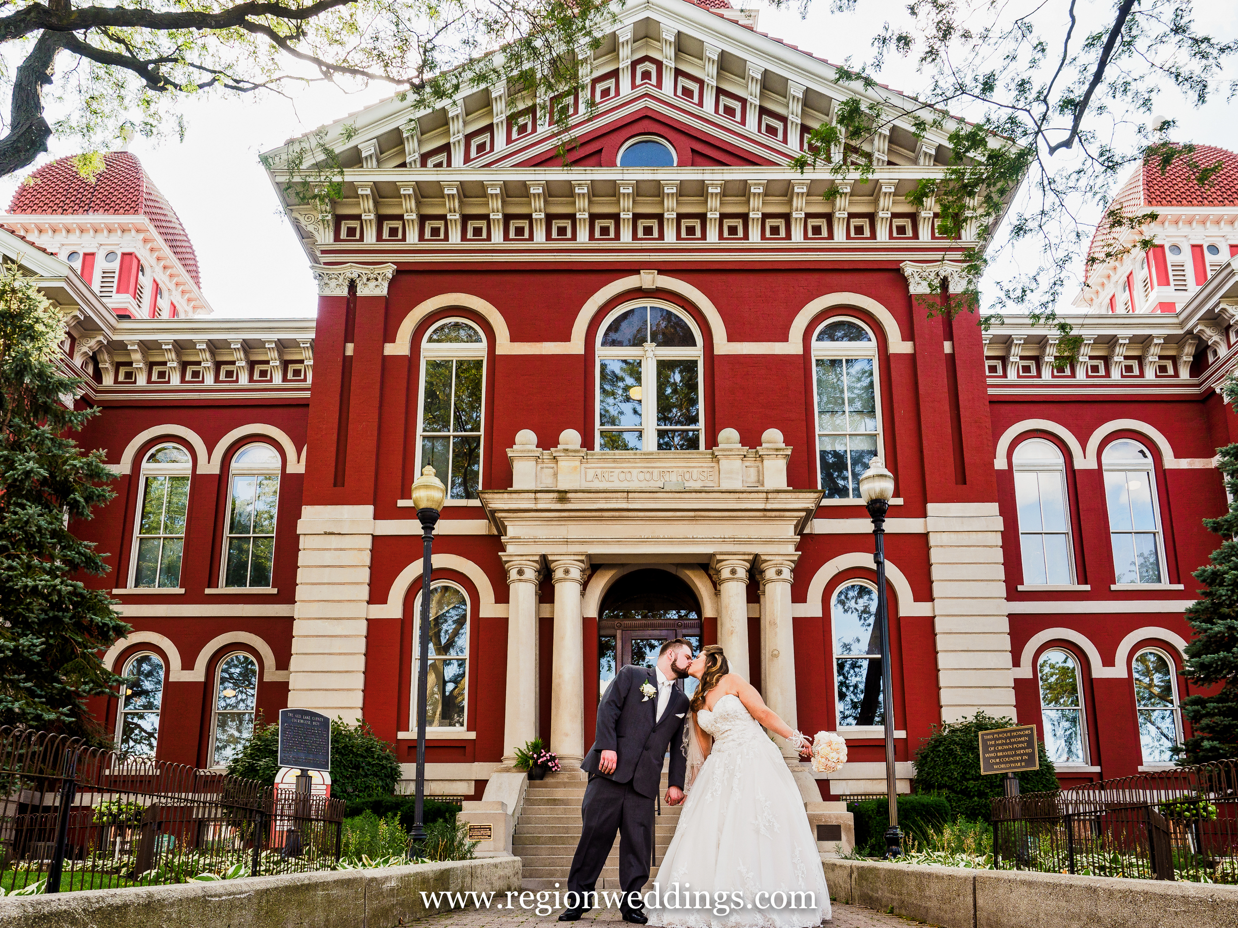 Bride and groom kiss in front of the old Crown Point Courthouse.