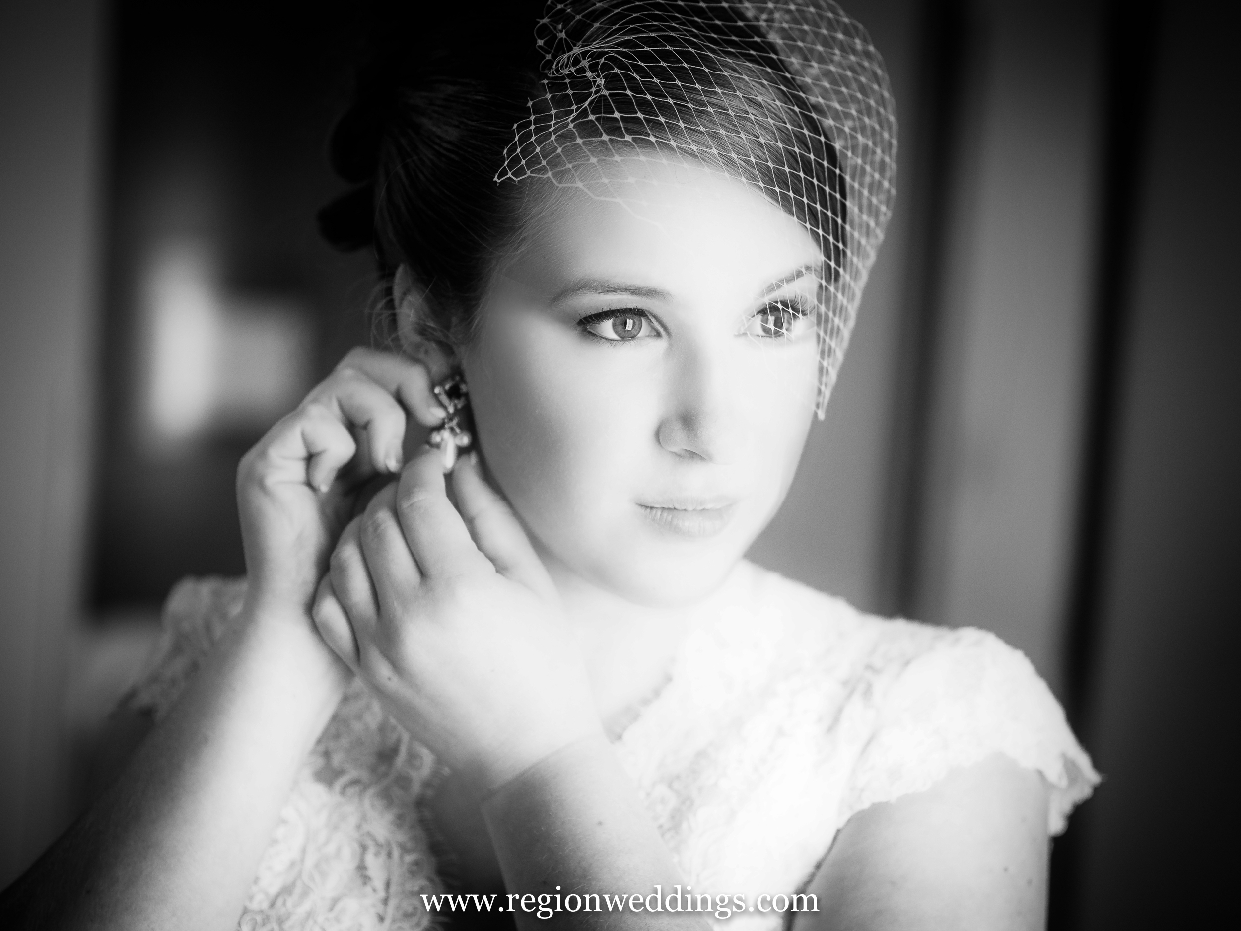 Bride gazes outside a window on her wedding day.