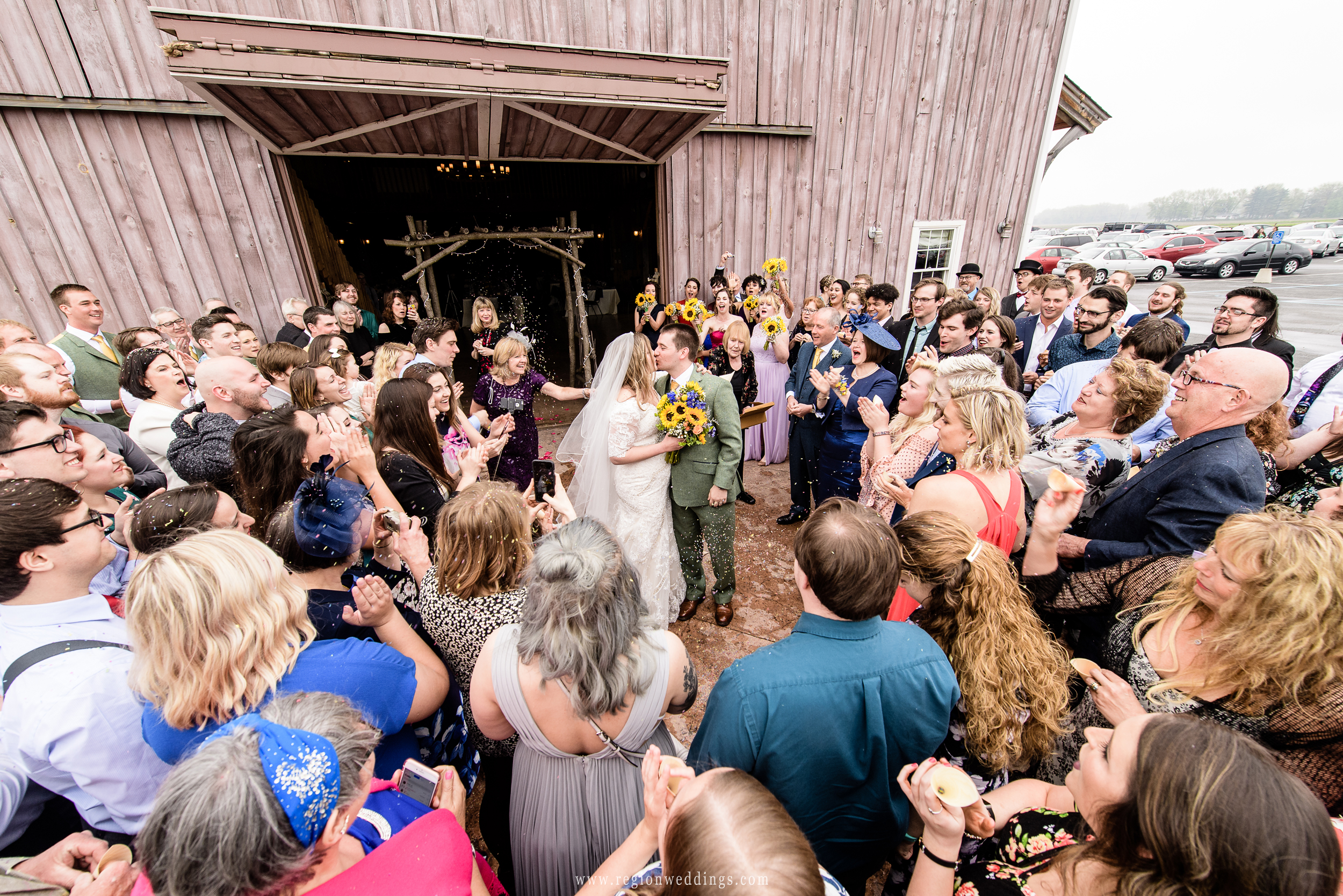 Bride and groom are congratulated with confetti at County Line Orchard.