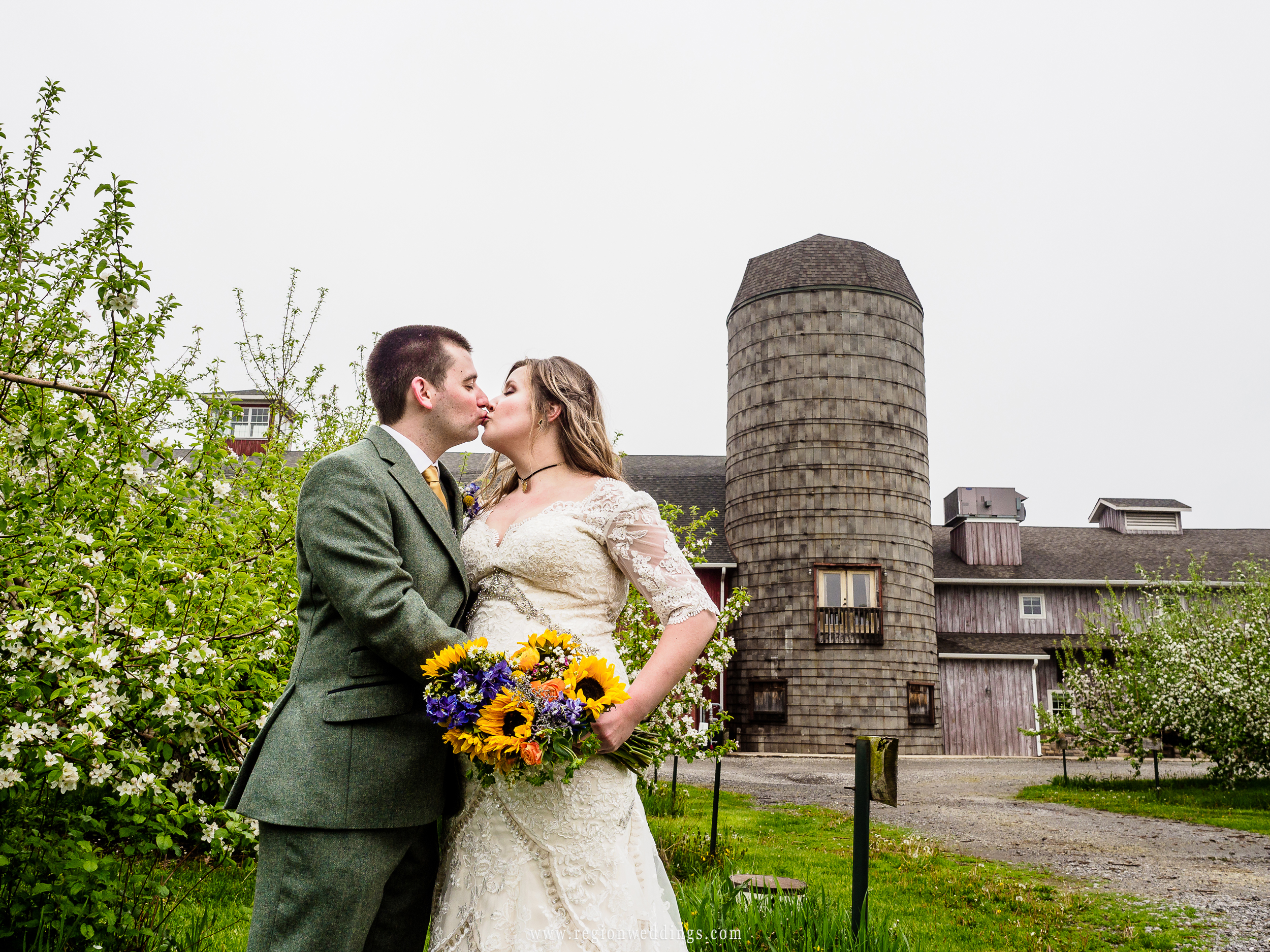Bride and groom kiss with the rustic grain silo in the background.