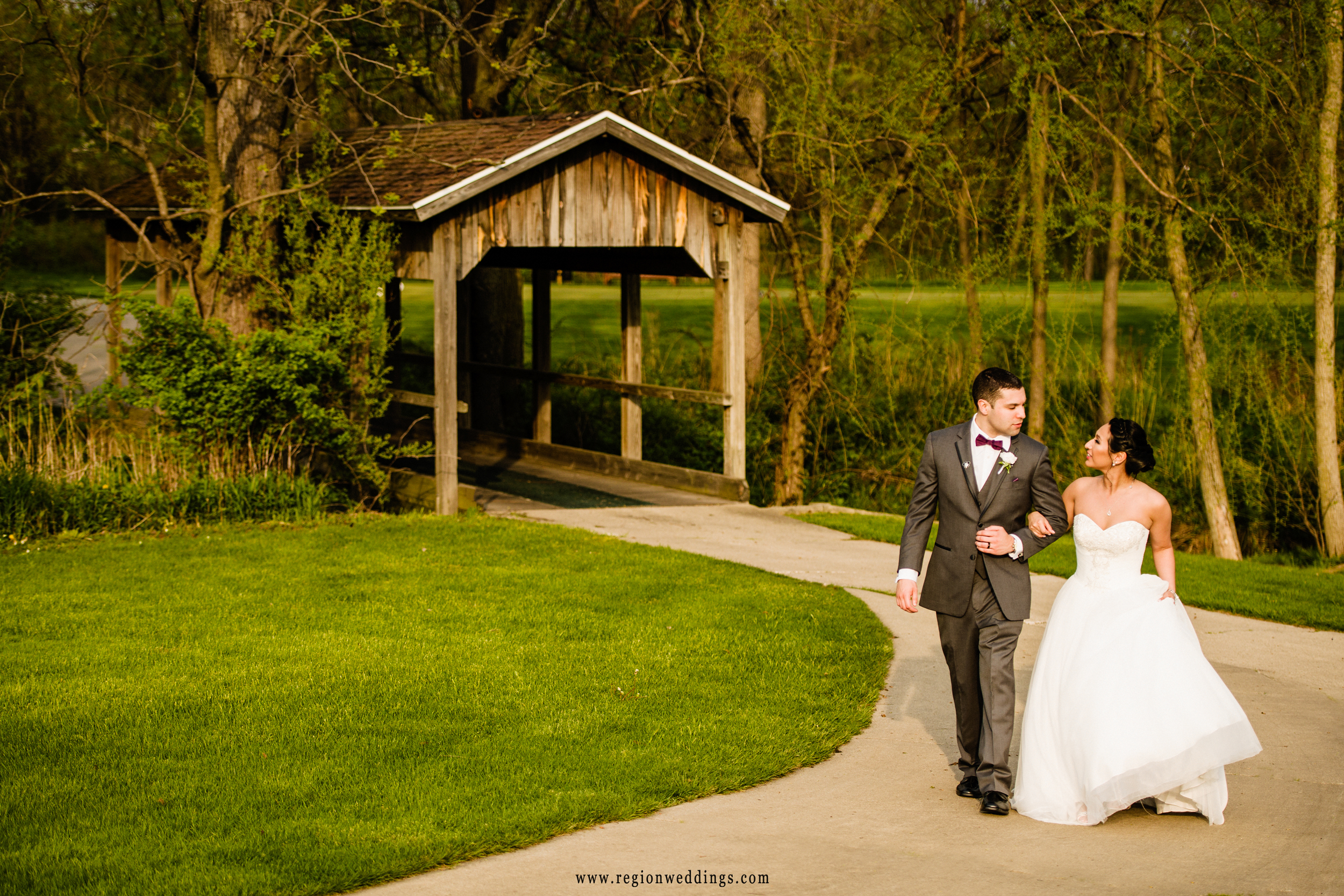 Bride and groom walk near the covered bridge at Sand Creek Country Club.