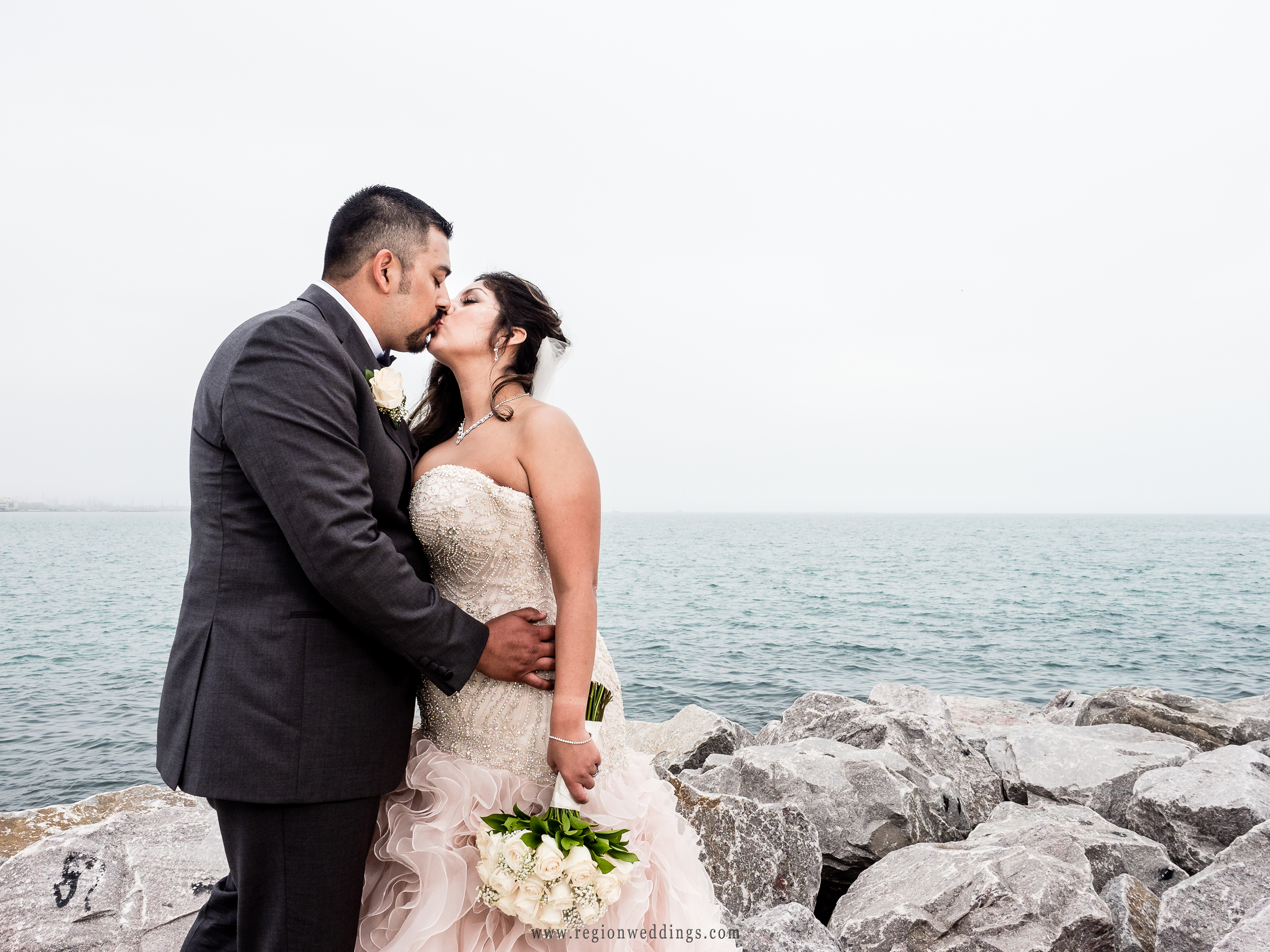 Bride and groom smooch atop the rocks at Whiting Lake Front Park shoreline.