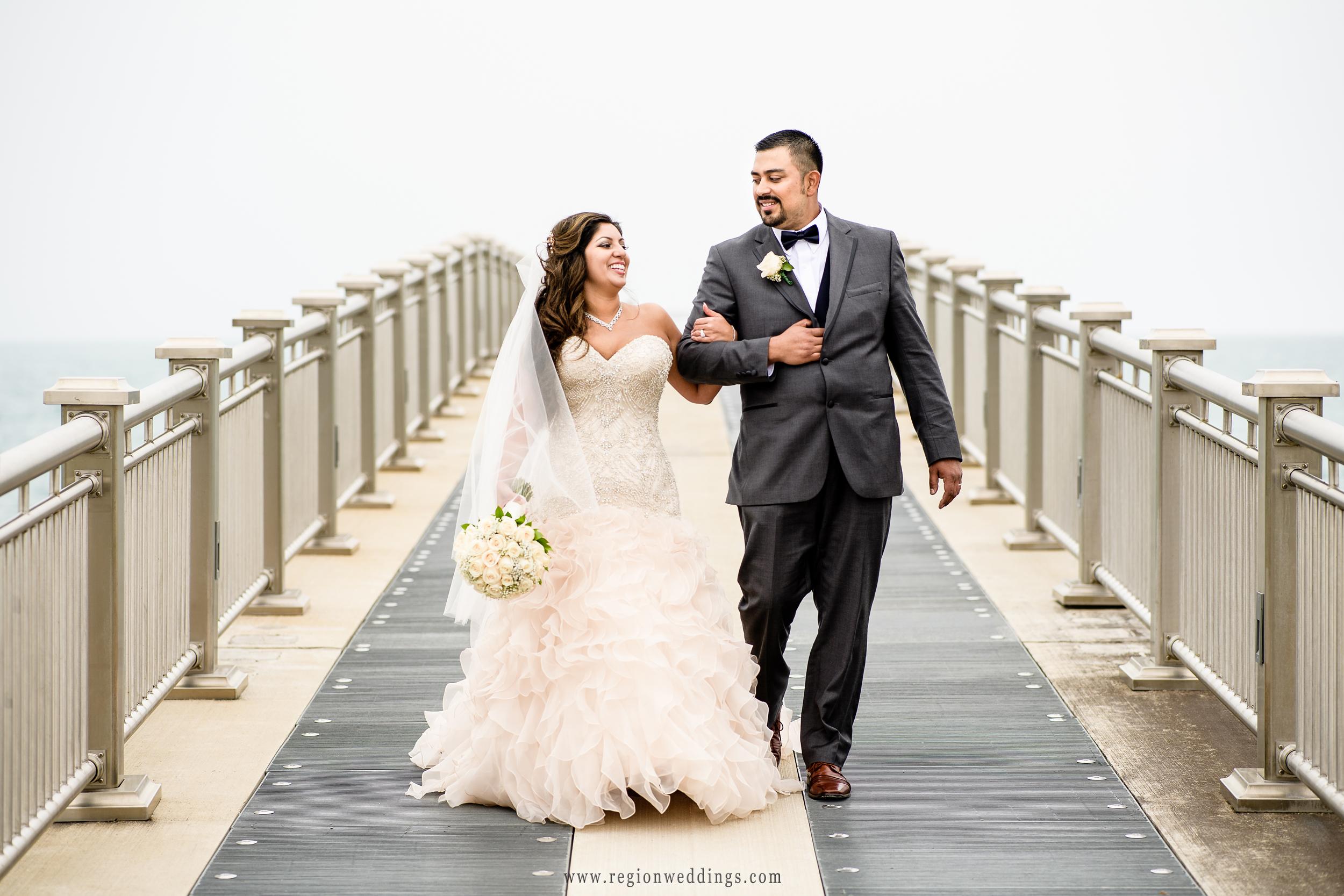 The groom escorts his bride along the pier.