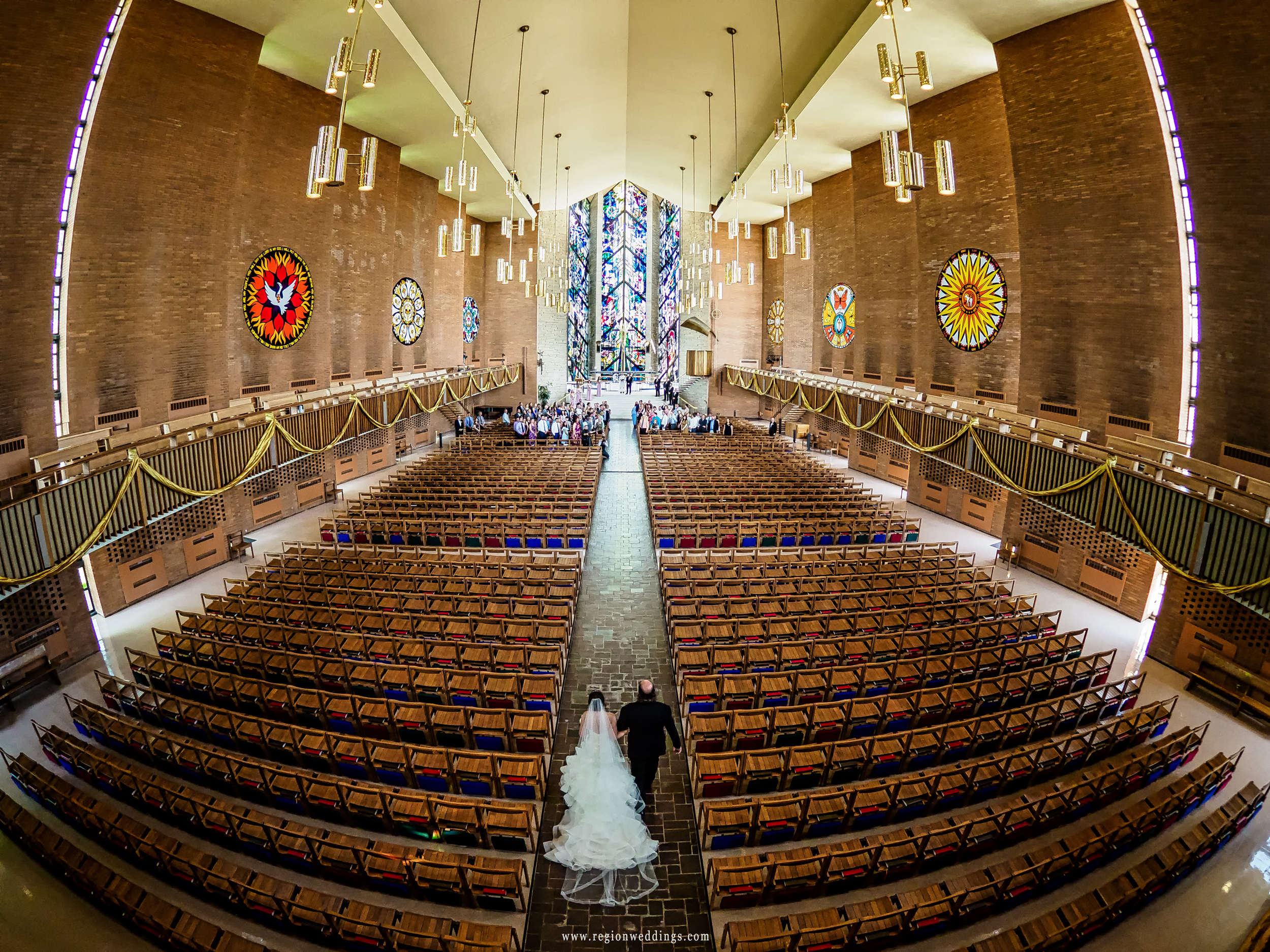 Father of the bride walks with his daughter at Chapel of the Resurrection.