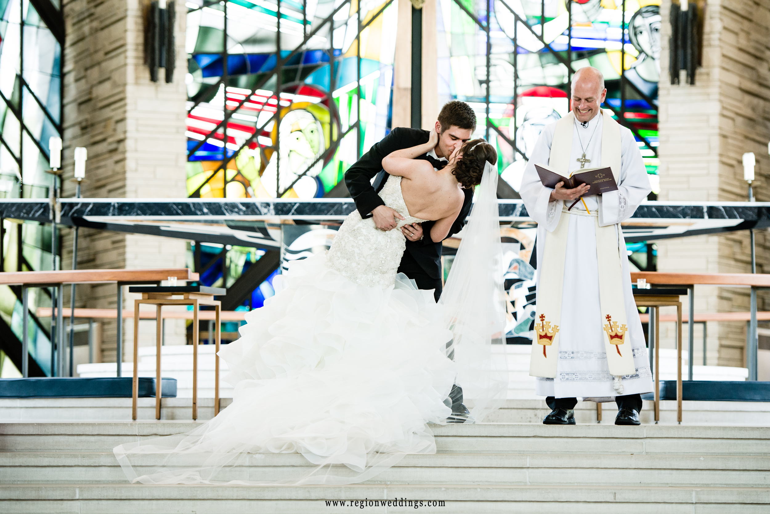 The groom dips his bride at the altar.